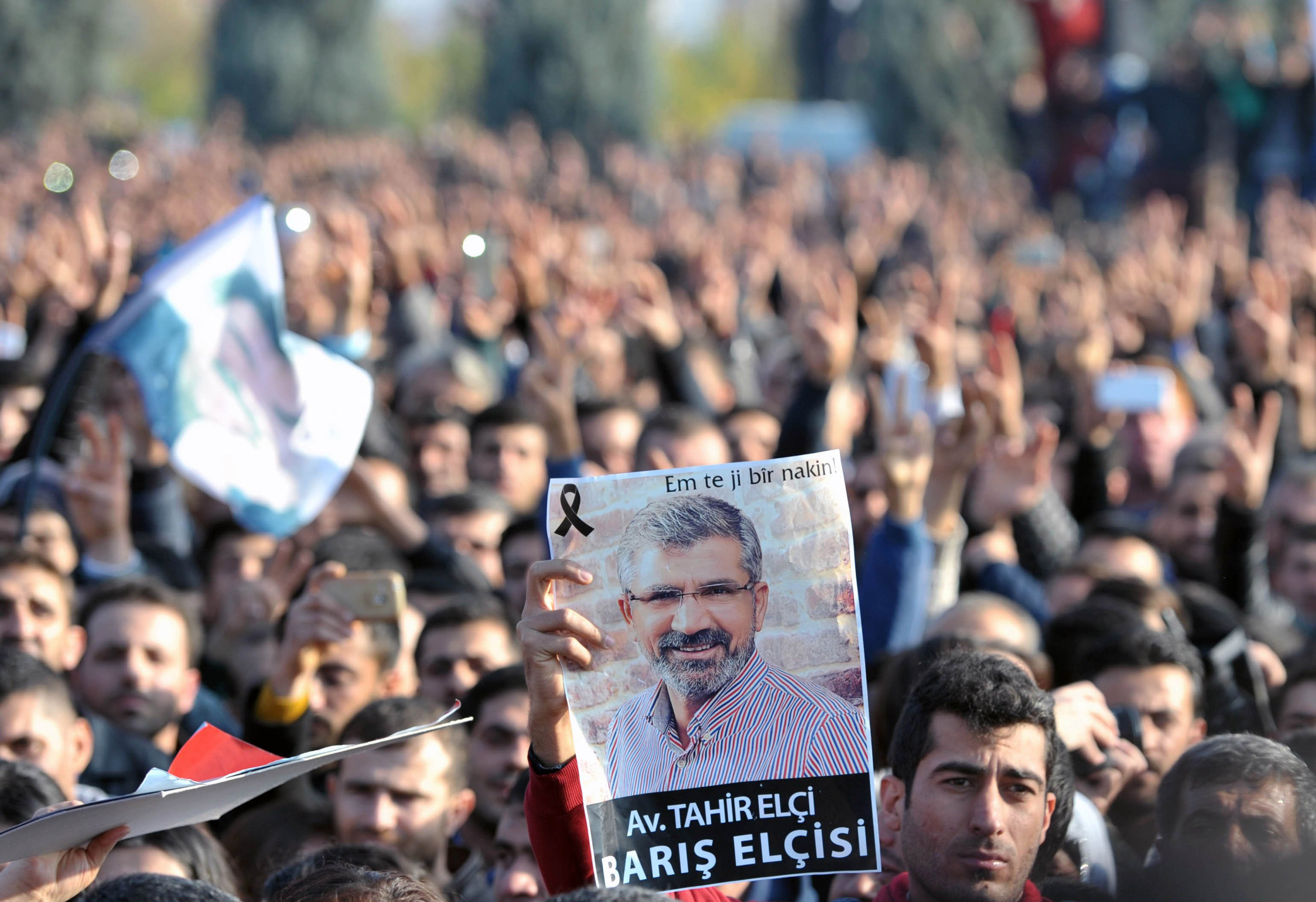 A man holds a portrait of Tahir Elci, head of the Diyarbakir Bar Association, during a mourning ceremony in Diyarbakir province, Turkey, on Nov. 29, 2015.