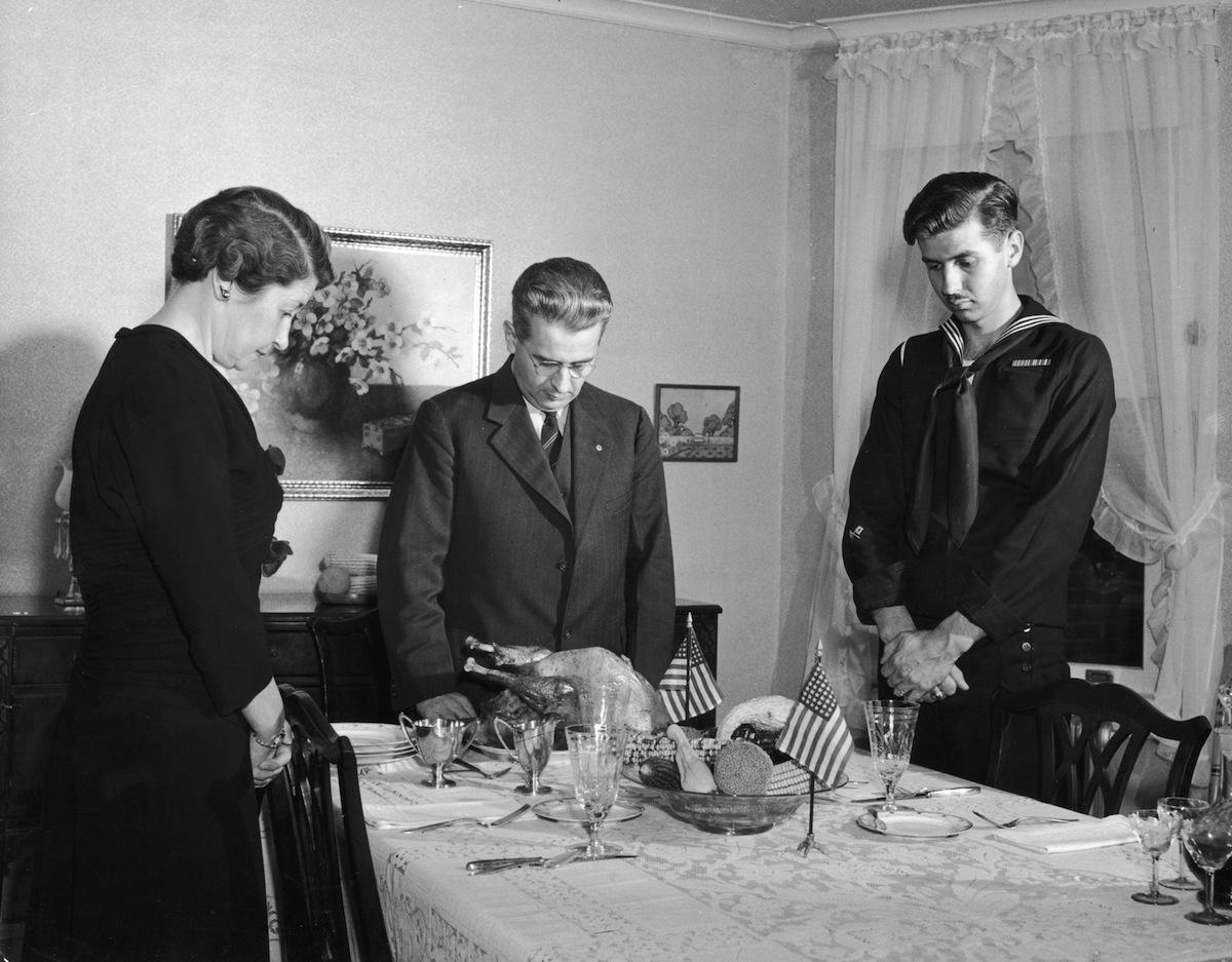 circa 1945:  A father, mother and their serviceman son stand around a dinner table with their heads bowed in prayer, preparing to eat Thanksgiving dinner.