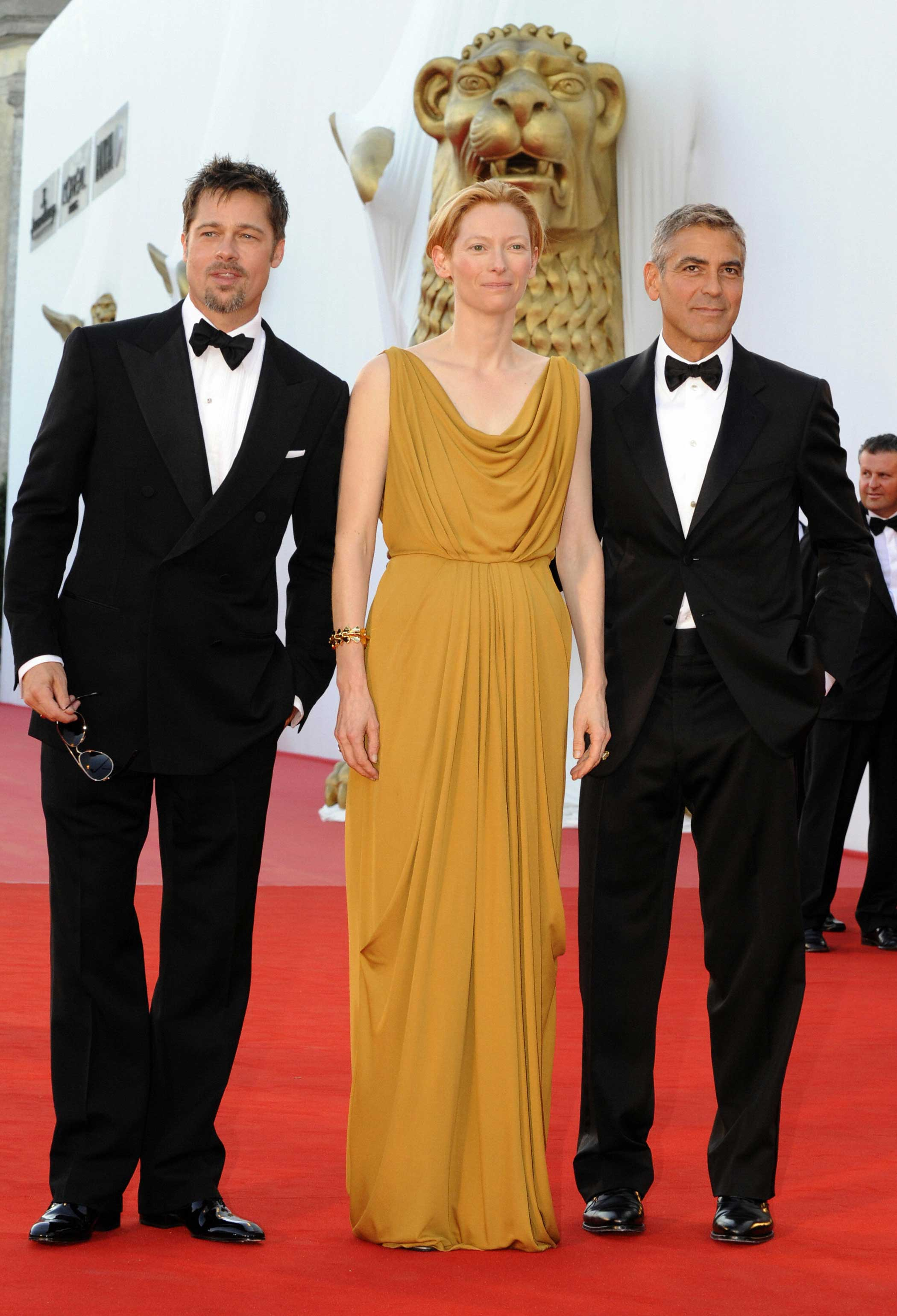 From left: Brad Pitt, Tilda Swinton, and George Clooney pose before the screening of Burn After Reading in Venice, Italy on Aug. 27, 2008.