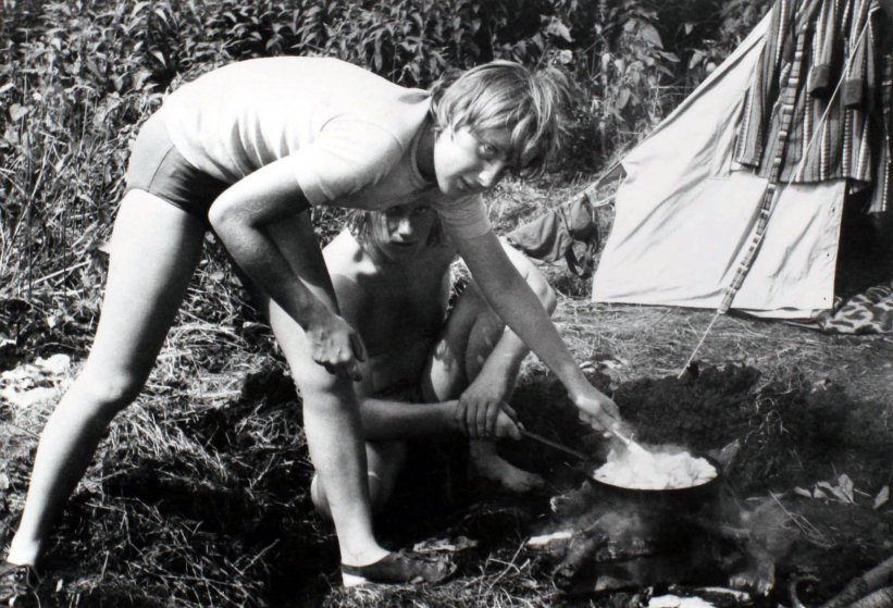 Angela Kasner prepares a meal on a campfire while camping with friends in Himmelpfort, German Democratic Republic on July 1973.