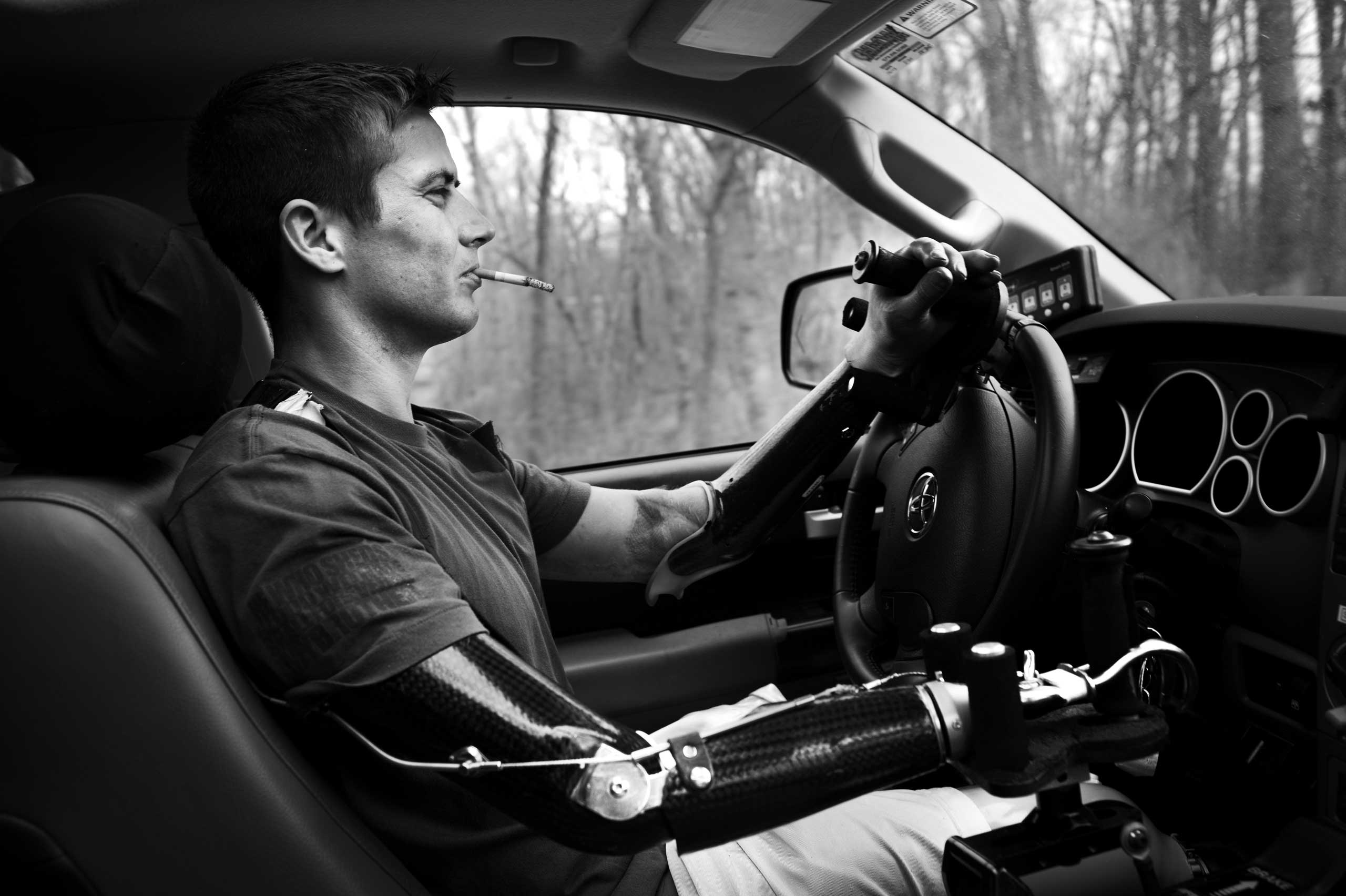 Cpl. Nicely driving his car, a custom-made pick-up adapted to be driven with his prosthesis. Lake Ozark, Miss., 2014.