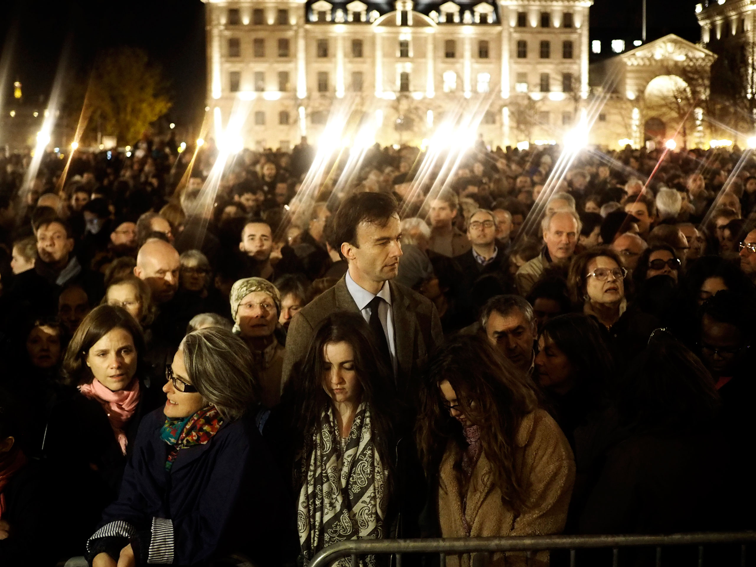 People gather outside of Notre Dame cathedral ahead of a ceremony in memory of the victims of the terrorist attacks in Paris, France. Nov. 15, 2015.