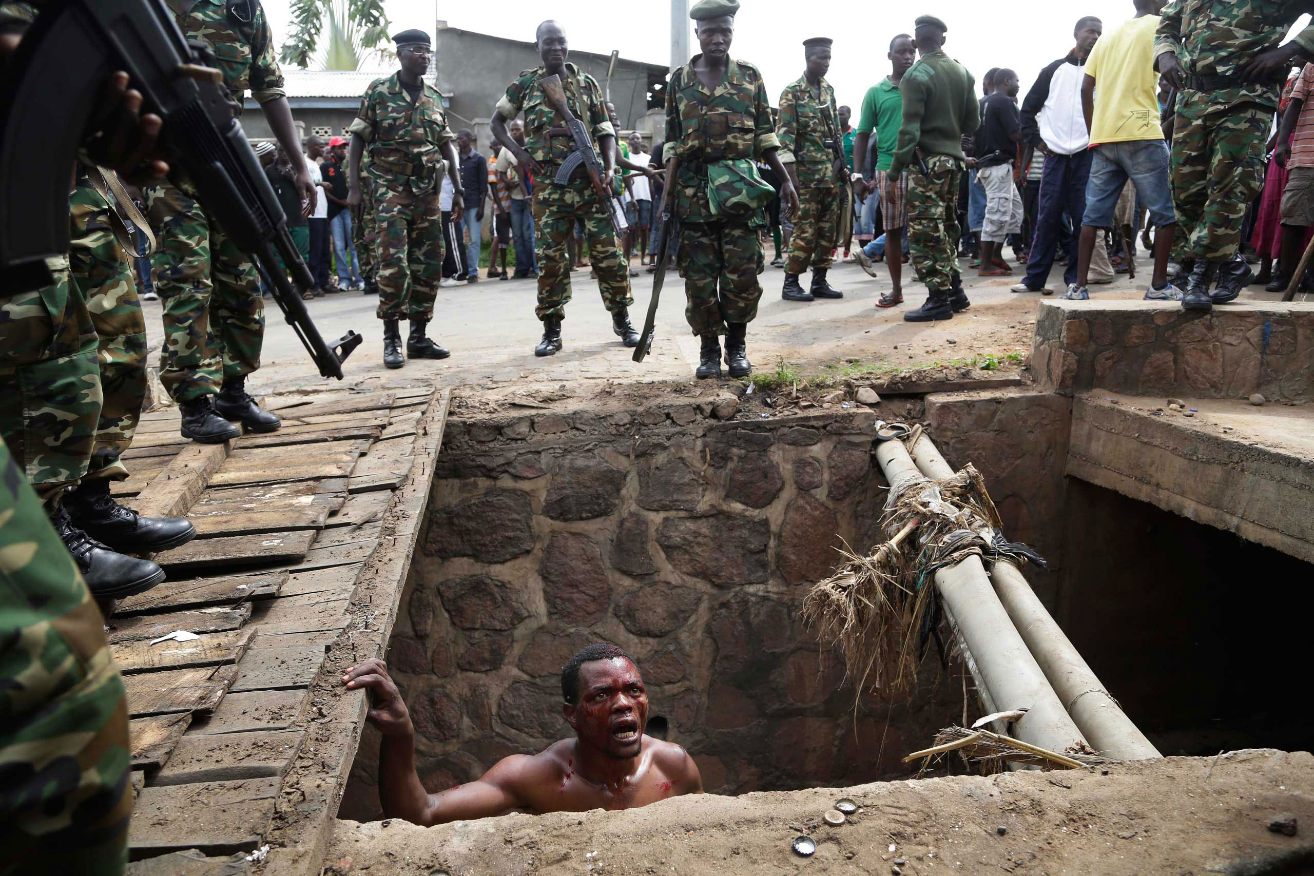 Jean Claude Niyonzima, a suspected member of the ruling party's Imbonerakure youth militia, pleads with soldiers to protect him from a mob of demonstrators after he emerged from hiding in a sewer in the Cibitoke district of Bujumbura, Burundi. Niyonzima escaped the lynching by running into the sewer. May 7, 2015.