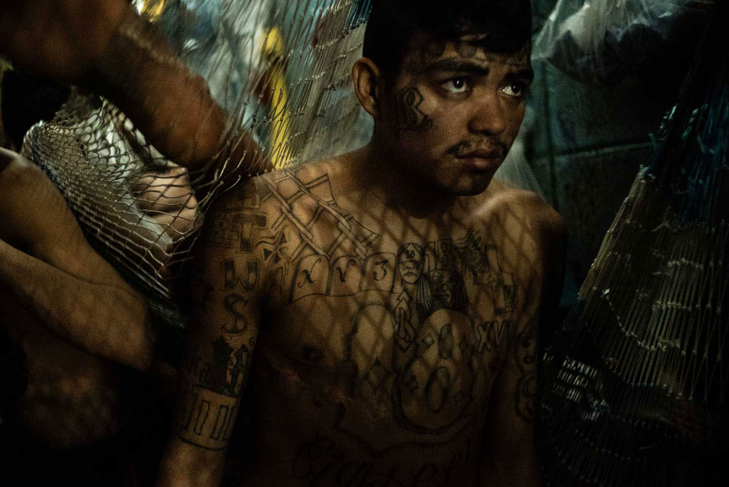 A cell inmate in the district of Soyapango, municipality in San Salvador, where police conducted a night raid in search of Mara Salvatrucha gang's members. Alleged gang members are handcuffed, identified, and then put into the barltolina, an overcrowded temporary cell at police headquarters.