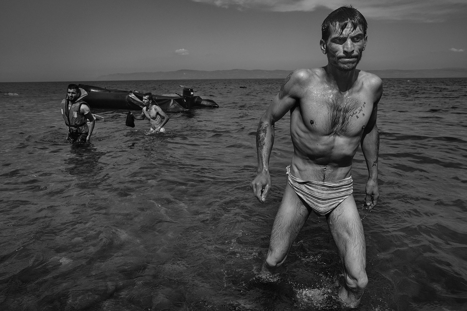 A migrant walks towards shore in Lesbos, Greece, after swimming from the inflatable boat he had taken in the crossing from Turkey.                                Refugees from Syria, Afghanistan, Pakistan, Somalia cross the sea between Turkey and to the island of Lesbos, as the first step in making their way across Europe. Sept. 27, 2015.
