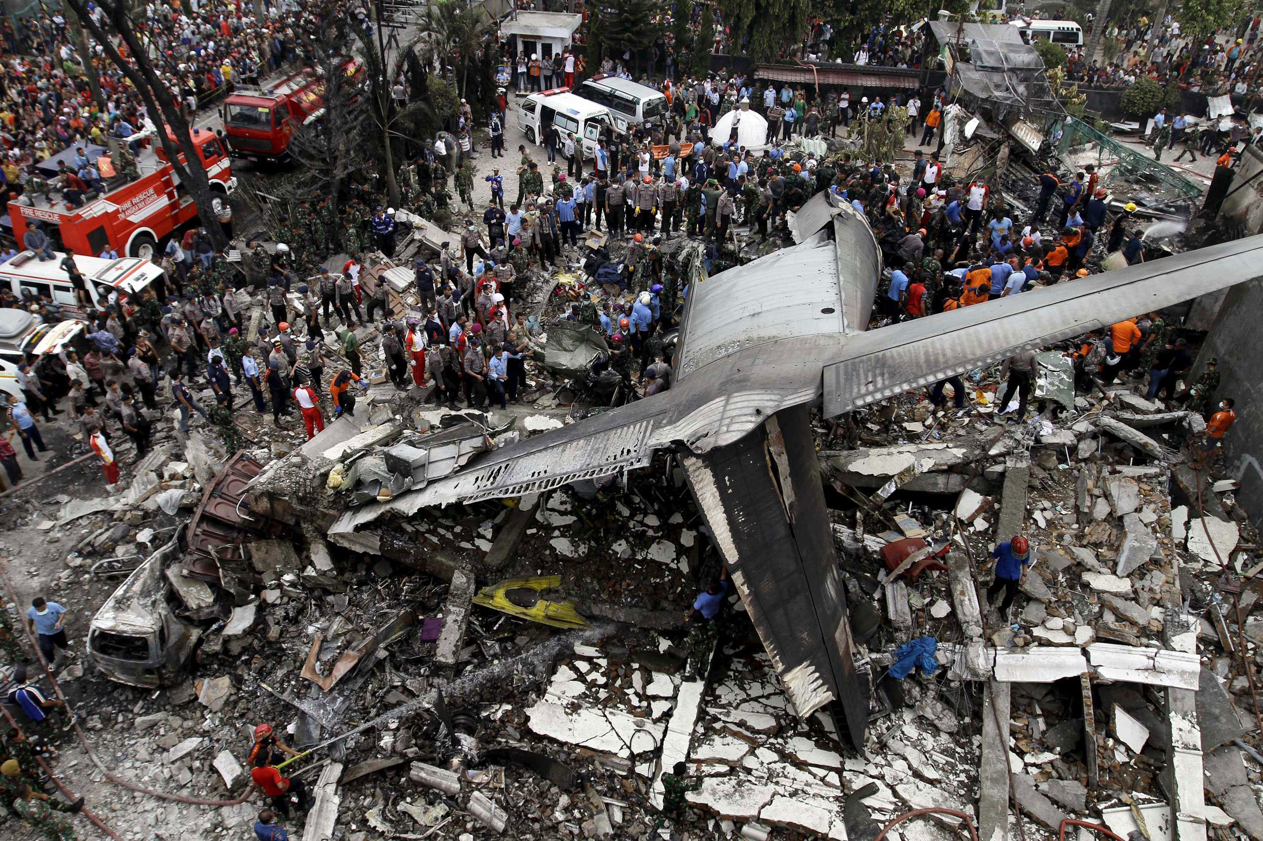 Security forces and rescue teams examine the wreckage of an Indonesian military C-130 Hercules transport plane after it crashed into a residential area in the North Sumatra city of Medan, Indonesia. June 30, 2015. At least 30 people were killed when the military transport plane crashed into a residential area two minutes after take-off in northern Indonesia, putting a fresh spotlight on the country's woeful air safety record.