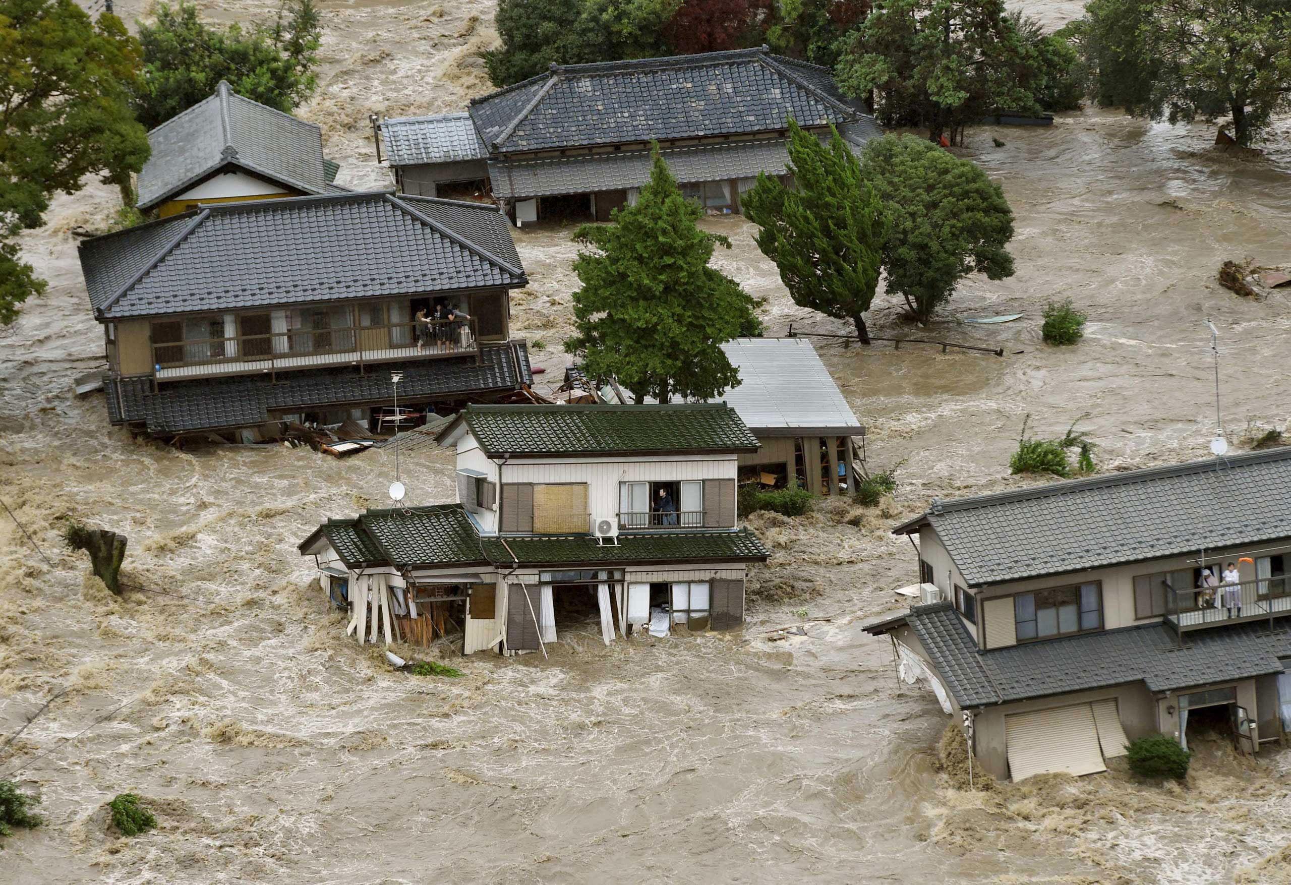 Residents wait for rescue helicopters at a flooded residential area as the Kinugawa river burst their banks, caused by typhoon Etau, in Joso, Ibaraki prefecture, Japan. Sept. 10, 2015.