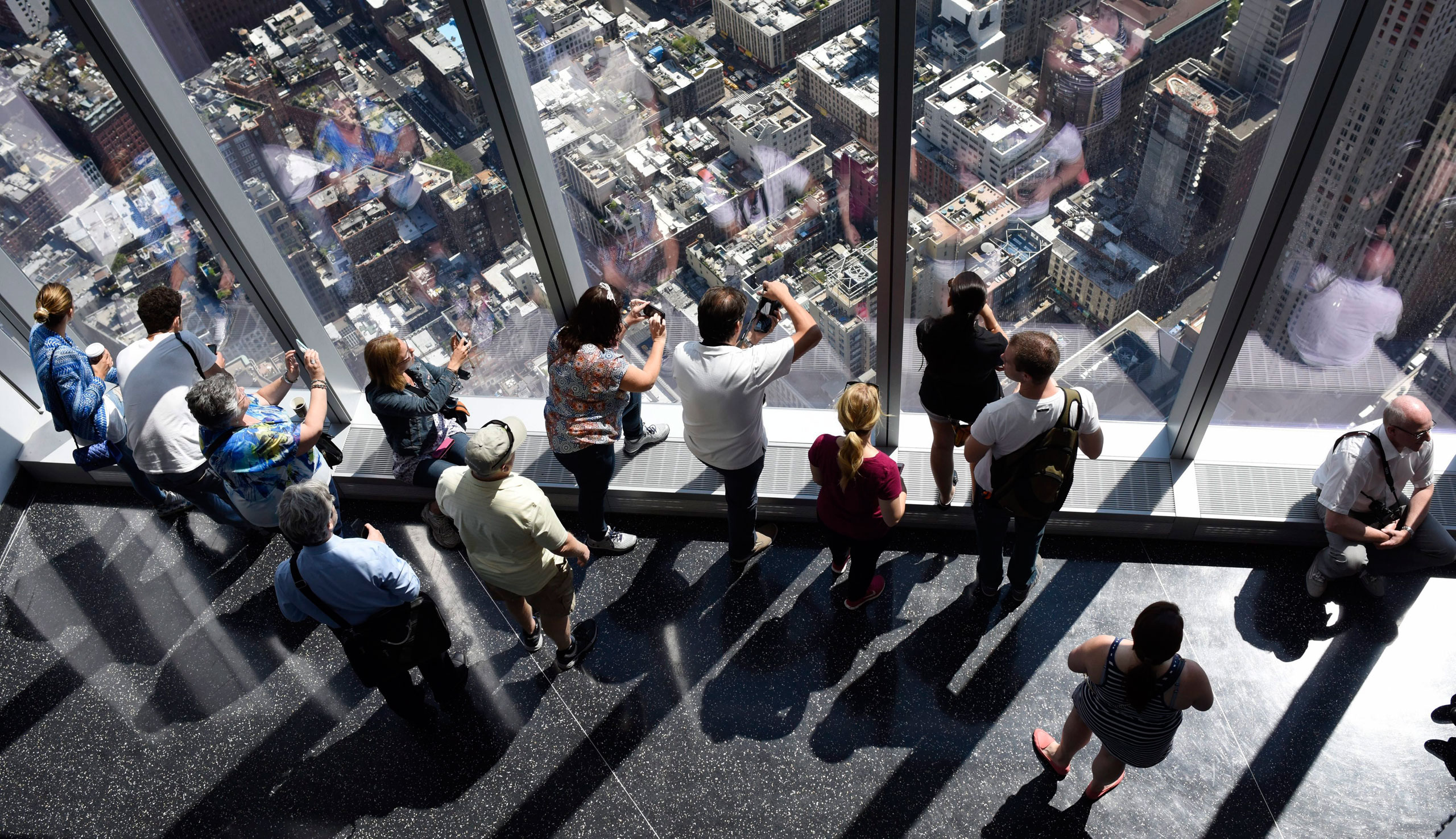 Visitors look out over city streets from the One World Observatory at One World Trade Center, in New York. May 29, 2015.