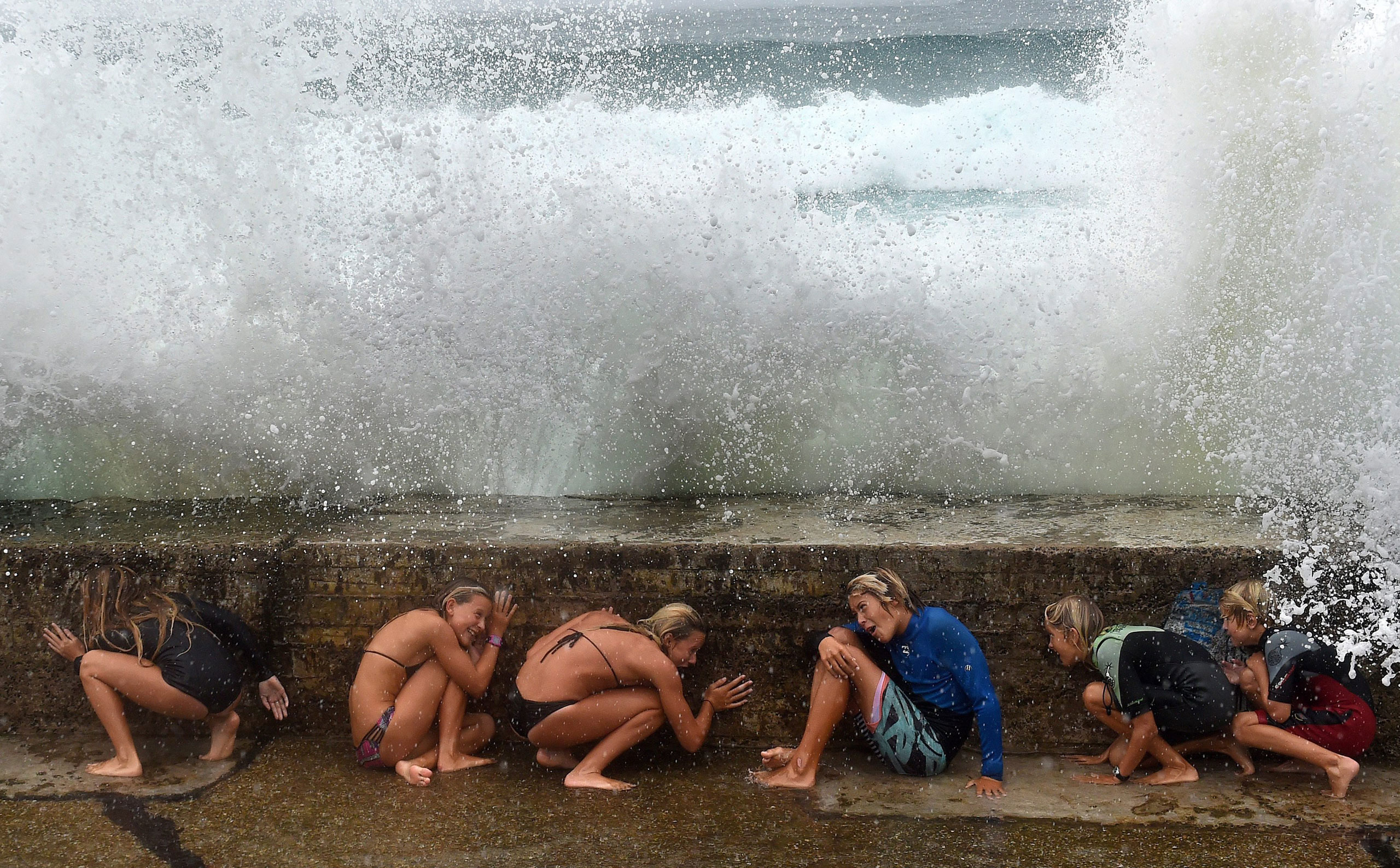 A young crowd takes shelter from big sea waves due to the Tropical Cyclone Marcia on the Gold Coast, Queensland, Australia. Feb. 20, 2015.