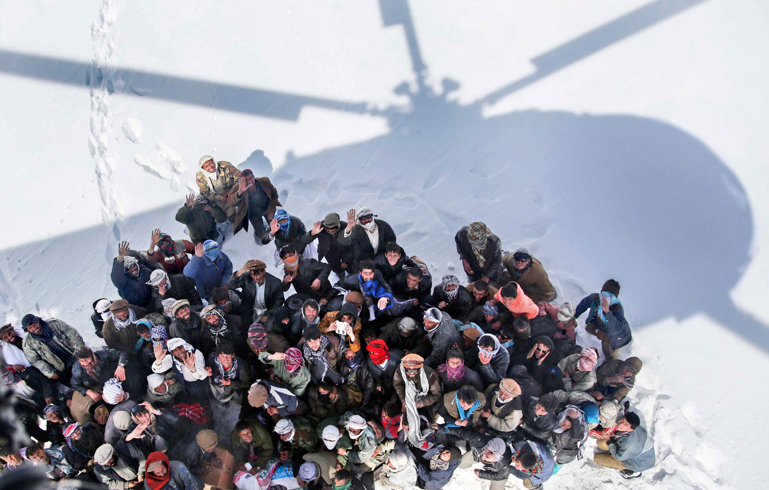 Survivors of an avalanche wait to receive relief goods distributed by an Army helicopter in the Paryan district of Panjshir province, Afghanistan. Feb. 28, 2015.