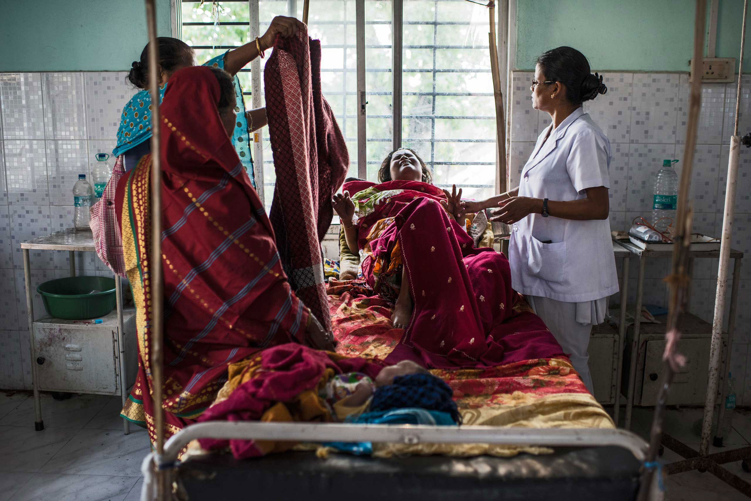 Nazreen Khatoon winces in pain as she lies gravely ill, suffering from severe postpartum anemia at the Tezpur Civil Hospital in Tezpur, Assam, India. April 2015.  Assam has the highest rate of women dying in chidbirth and from pregnancy-related causes in all of India, where roughly 50,000 women die annually in childbirth across the country.  Many families in Assam work on the tea plantations, where there is a high rate of pregnant and lactating women who are severely anemic due to poor diets and little to no prenatal care, leading to a high number of pregnancy complications.
