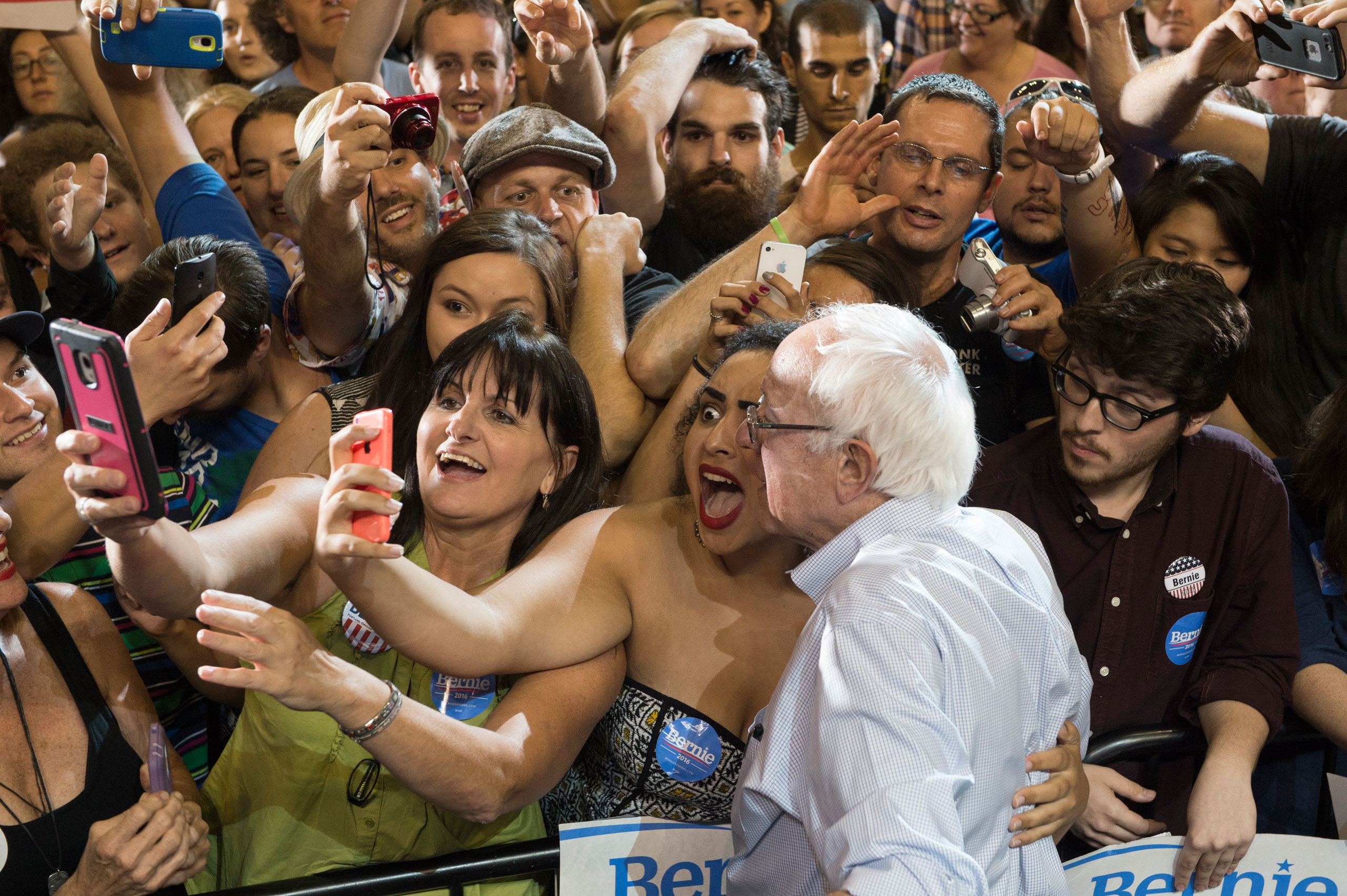 Naomi Scott, center, of McMinnville, Ore., takes a picture with Democratic presidential candidate Senator Bernie Sanders, I-Vt., at a rally at the Moda Center in Portland, Ore. Aug. 9, 2015.