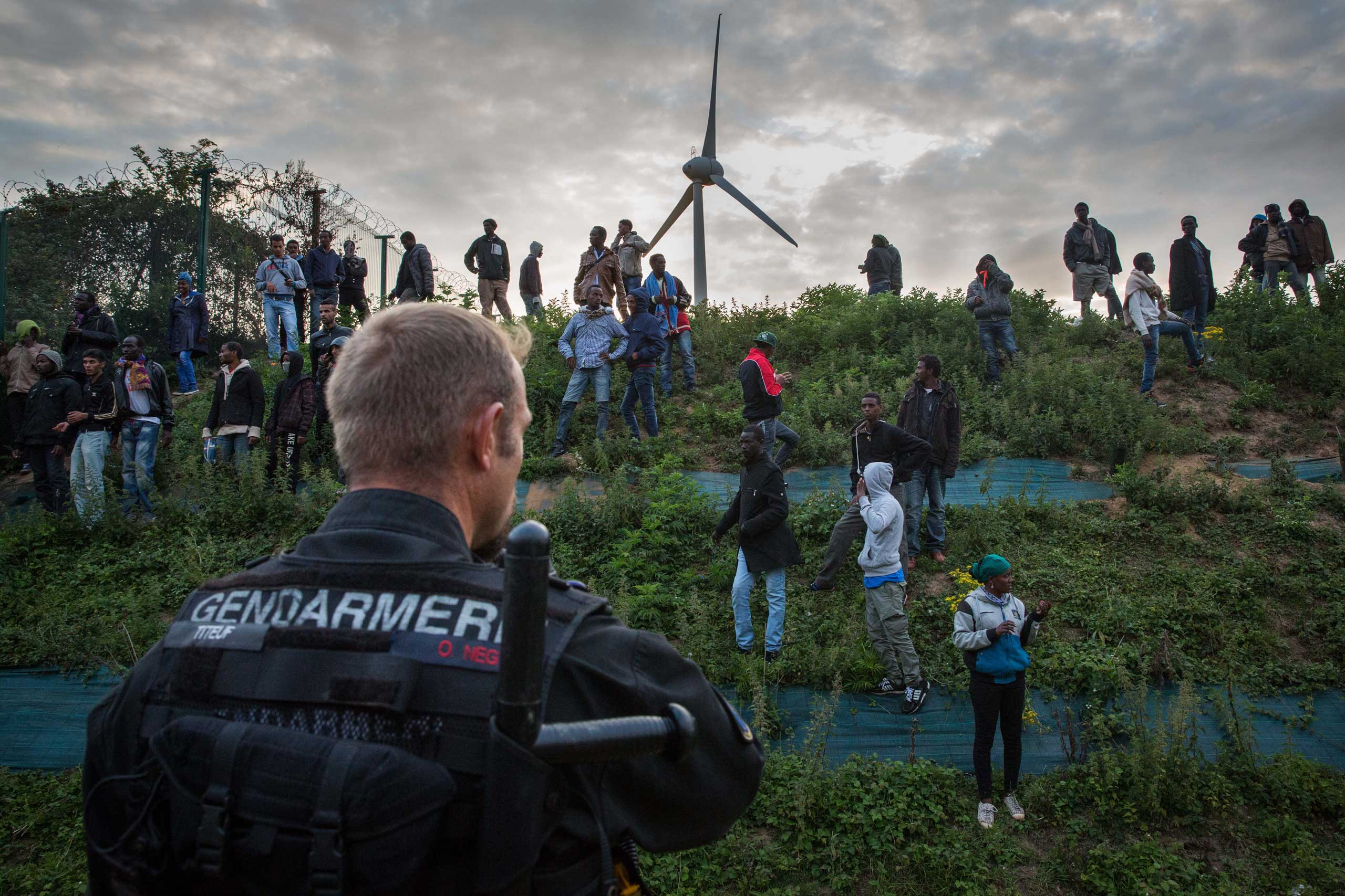 Gendarmerie attempt to prevent people from entering the Eurotunnel terminal in Coquelles in Calais, France. Hundreds of migrants were trying to enter the Channel Tunnel and onto trains heading to the United Kingdom. July 30, 2015.