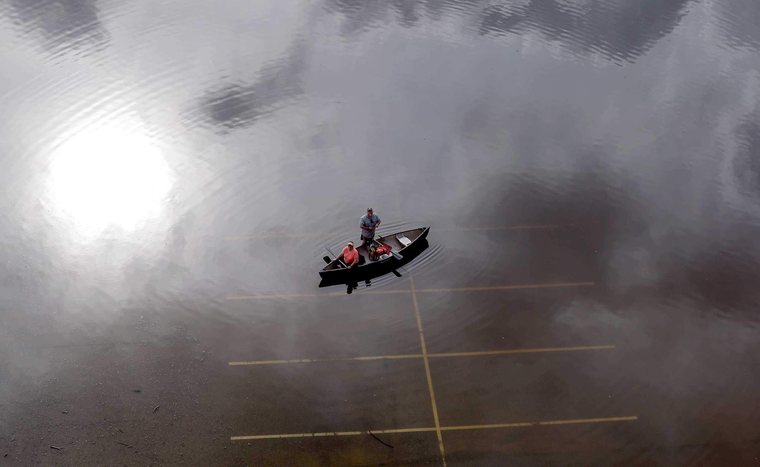 In this aerial photo, people prepare to launch a canoe from a flooded parking lot near Bear Creek Park in Houston, Texas. The Colorado River in Wharton and the Brazos and San Jacinto rivers near Houston are the main focus of concern as floodwaters moved from North and Central Texas downstream toward the Gulf of Mexico. May 30, 2015.