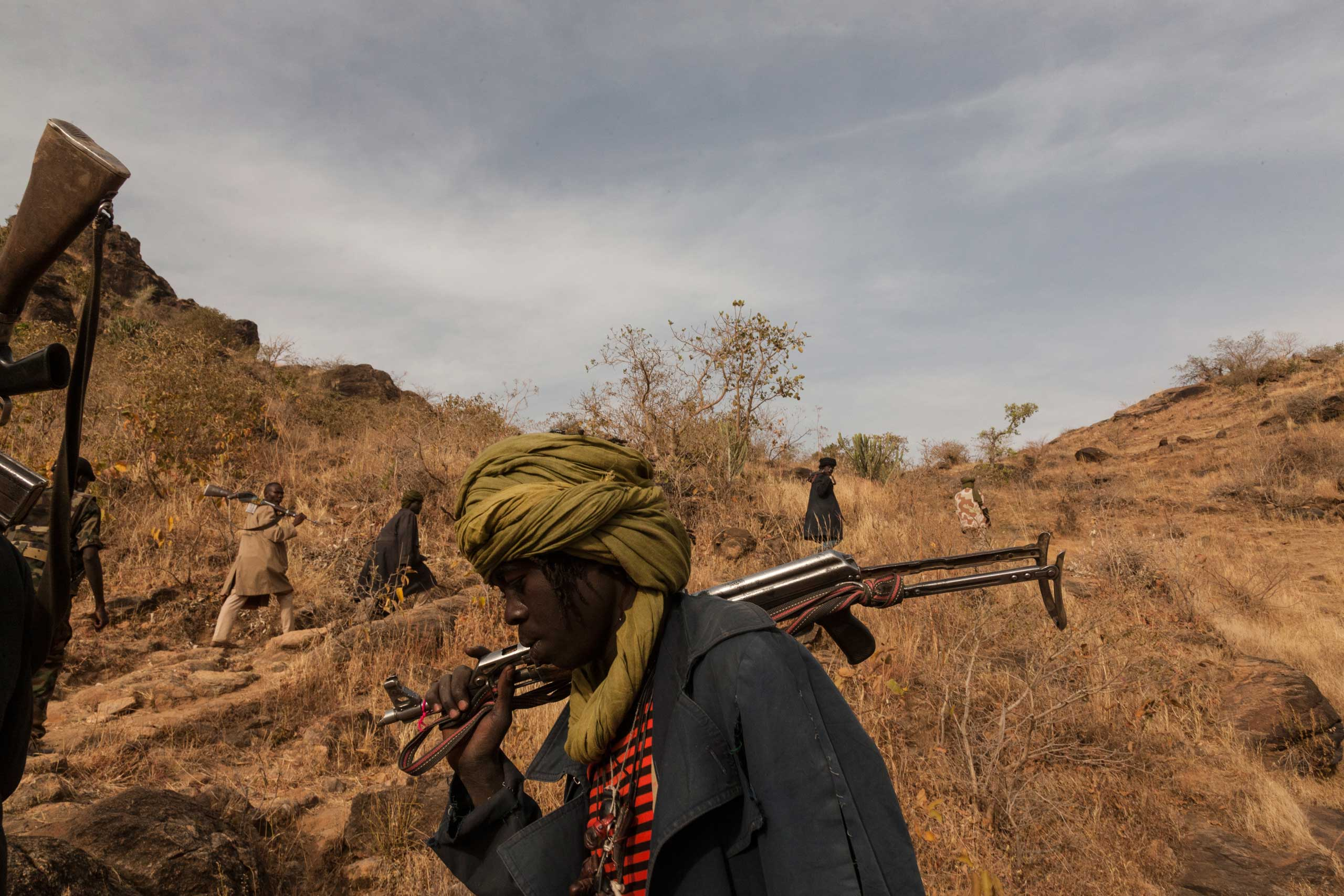 Members of the rebel group, the Sudan Liberation Army led by Abdul Wahid (SLA-AW), climb towards the front lines in Jebel Marra, Central Darfur, Sudan.  The mountainous area has been a stronghold of the SLA-AW since the conflict between the neglected population and the Sudanese government broke out in 2003. March 4, 2015.