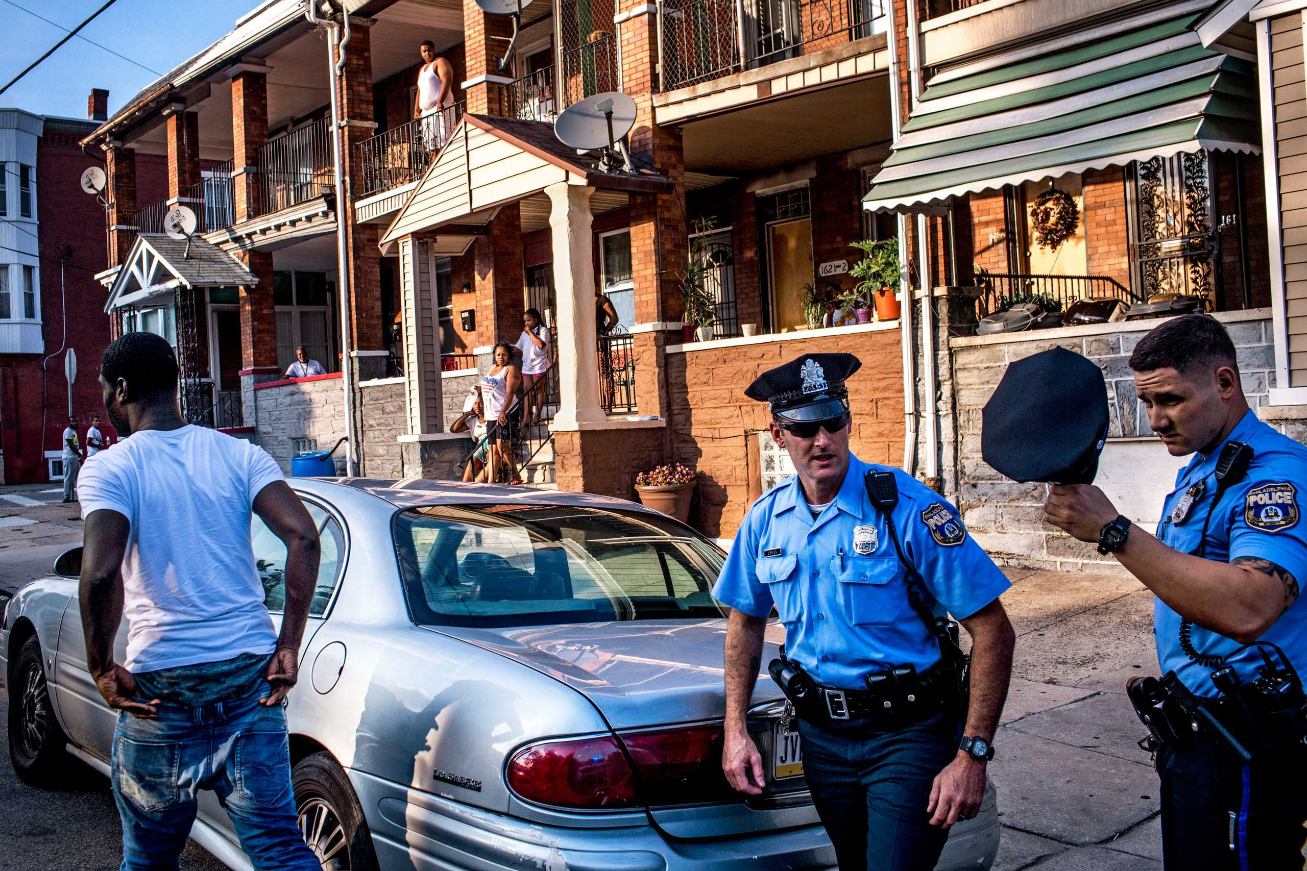 Officers Paul Watson, right, and his partner Officer Richard O'Brien make a traffic stop in Philadelphia, PA., as neighbors look on. After the police searched his car, the man was released. July 29, 2015.