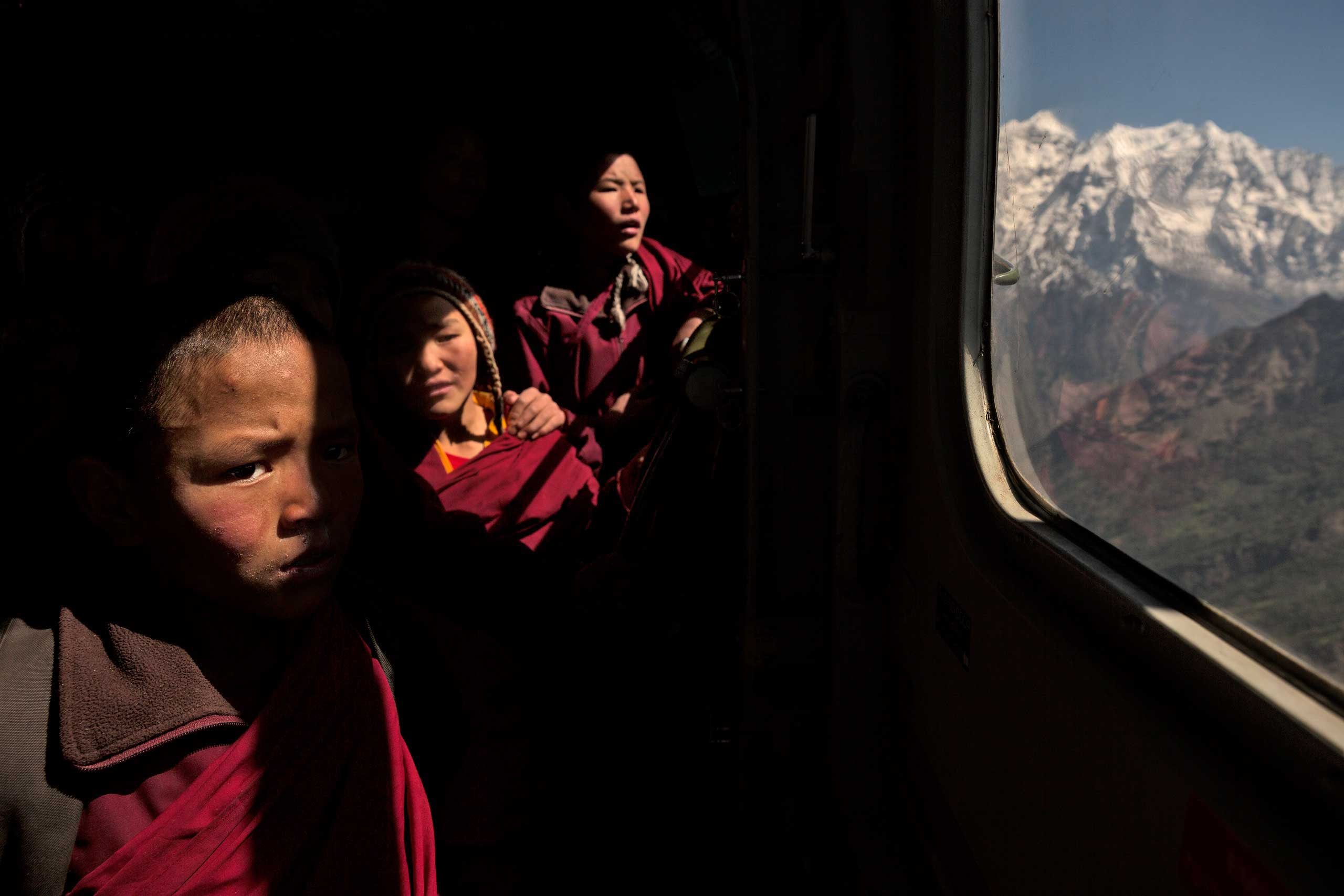 Young Buddhist monks gaze out of a helicopter as they are evacuated by the Indian army from a monastery in the Himalayas. May 2, 2015.