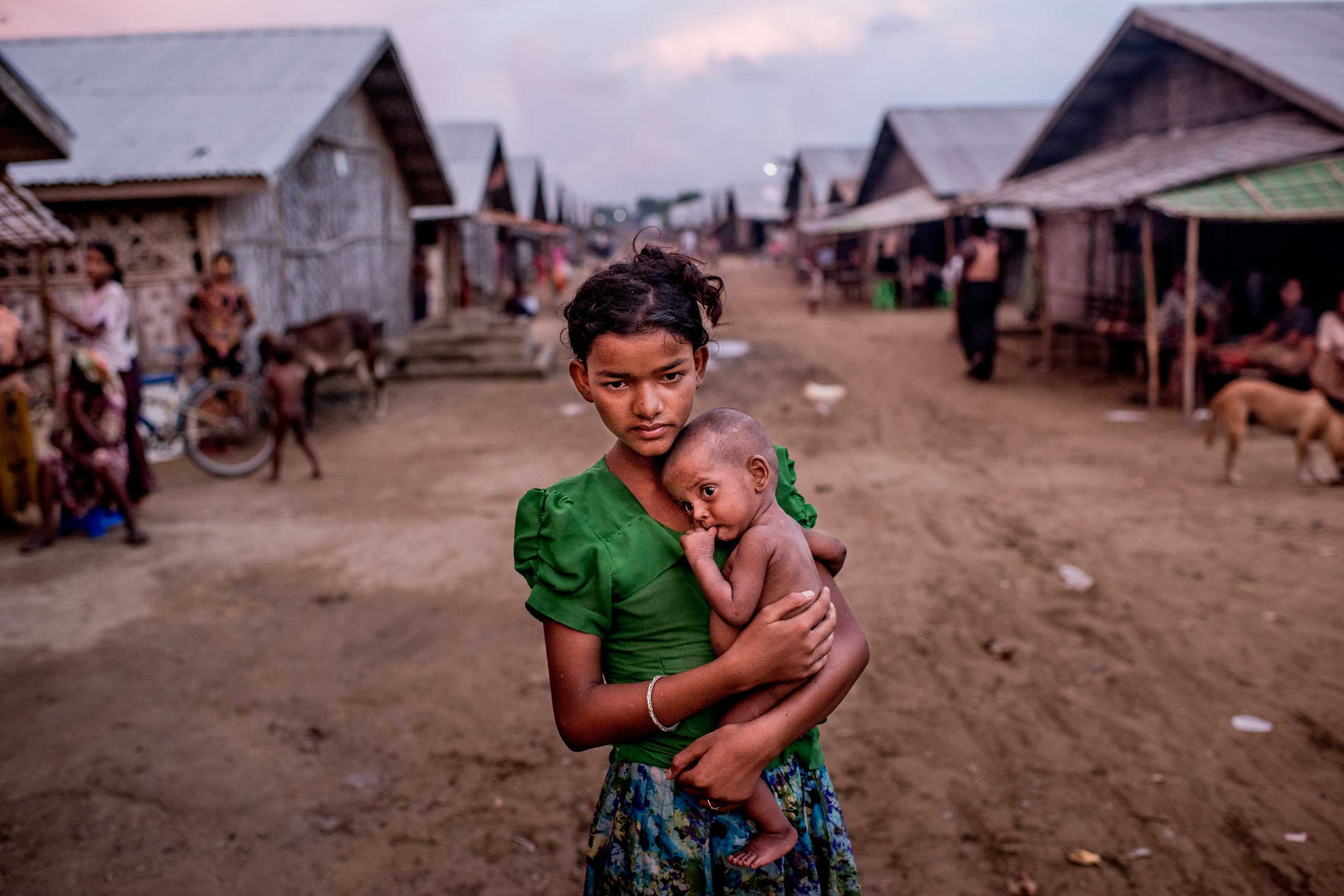 Oma Salema, 12, holds her undernourished brother Ayub Khan, 1, at a camp for Rohingya in Sittwe, Myanmar. The government of Myanmar says it is determined to stop the departures of migrants fleeing religious persecution in places like Sittwe, but it will not budge in its refusal to address the conditions driving the exodus across the sea. June 5, 2015.