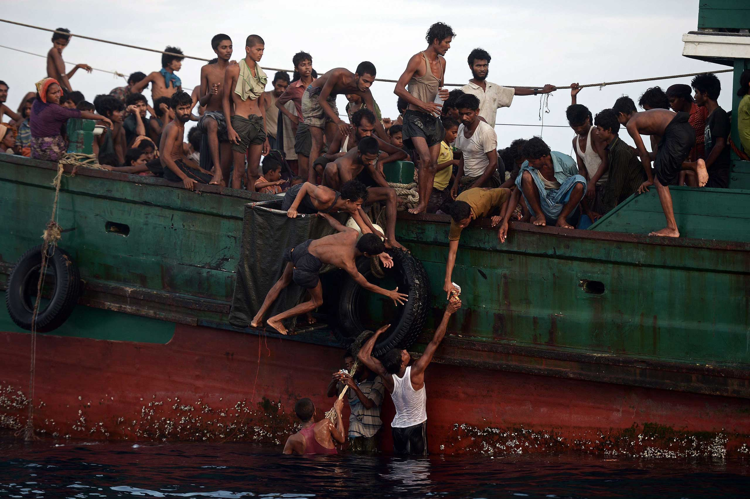 Rohingya migrants pass food supplies dropped by a Thai army helicopter to others aboard a boat drifting in Thai waters off the southern island of Koh Lipe in the Andaman sea.  A boat crammed with scores of Rohingya migrants—including many young children—was found drifting in Thai waters, with passengers saying several people had died over the last few days. May 14, 2015.
