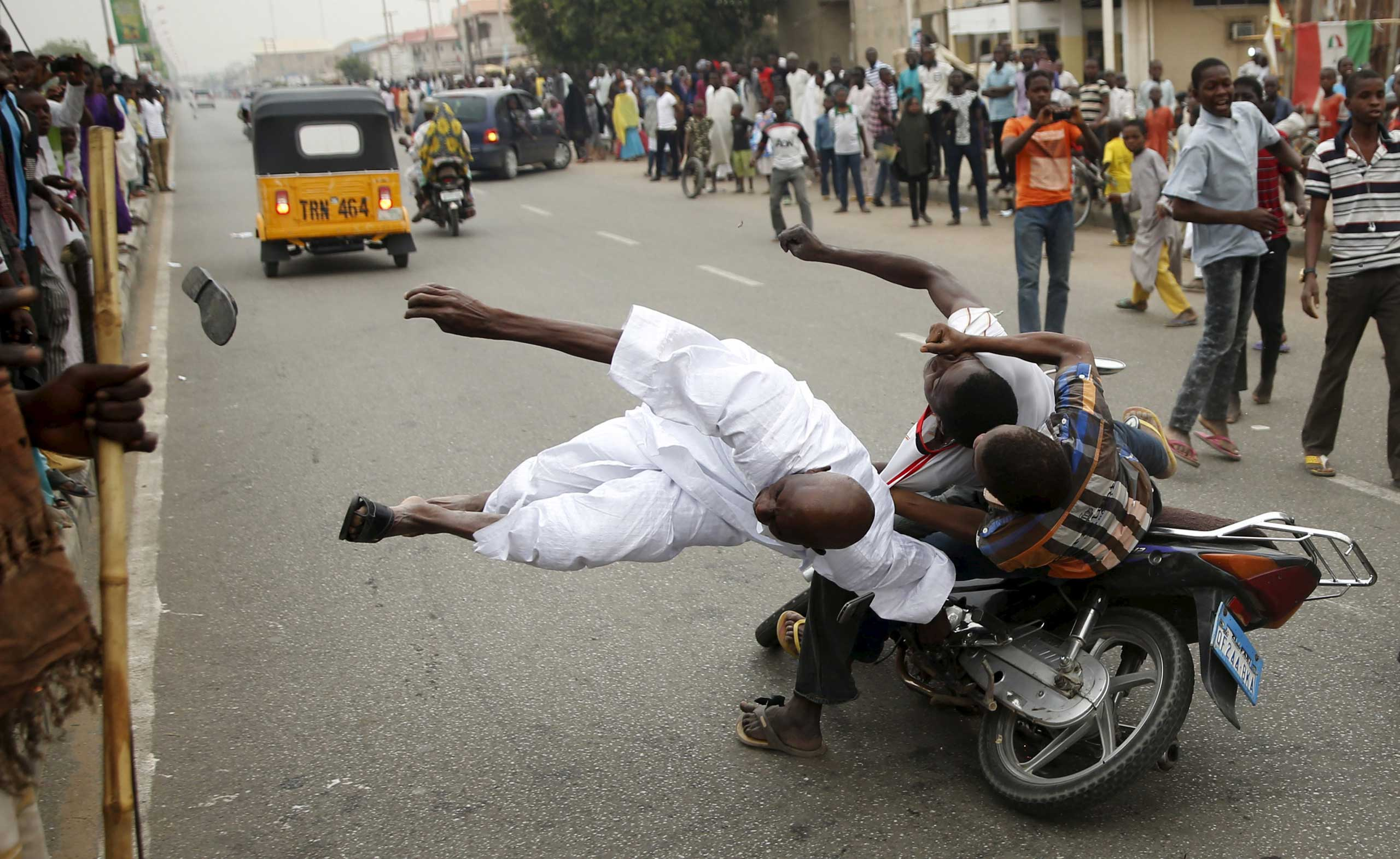 Supporters of the presidential candidate Muhammadu Buhari and his All Progressive Congress hit another supporter with a motorbike during celebrations in Kano. Nigeria's opposition APC declared an election victory for former military ruler Buhari and said Africa's most populous nation was witnessing history with its first democratic transfer of power. March 31, 2015.