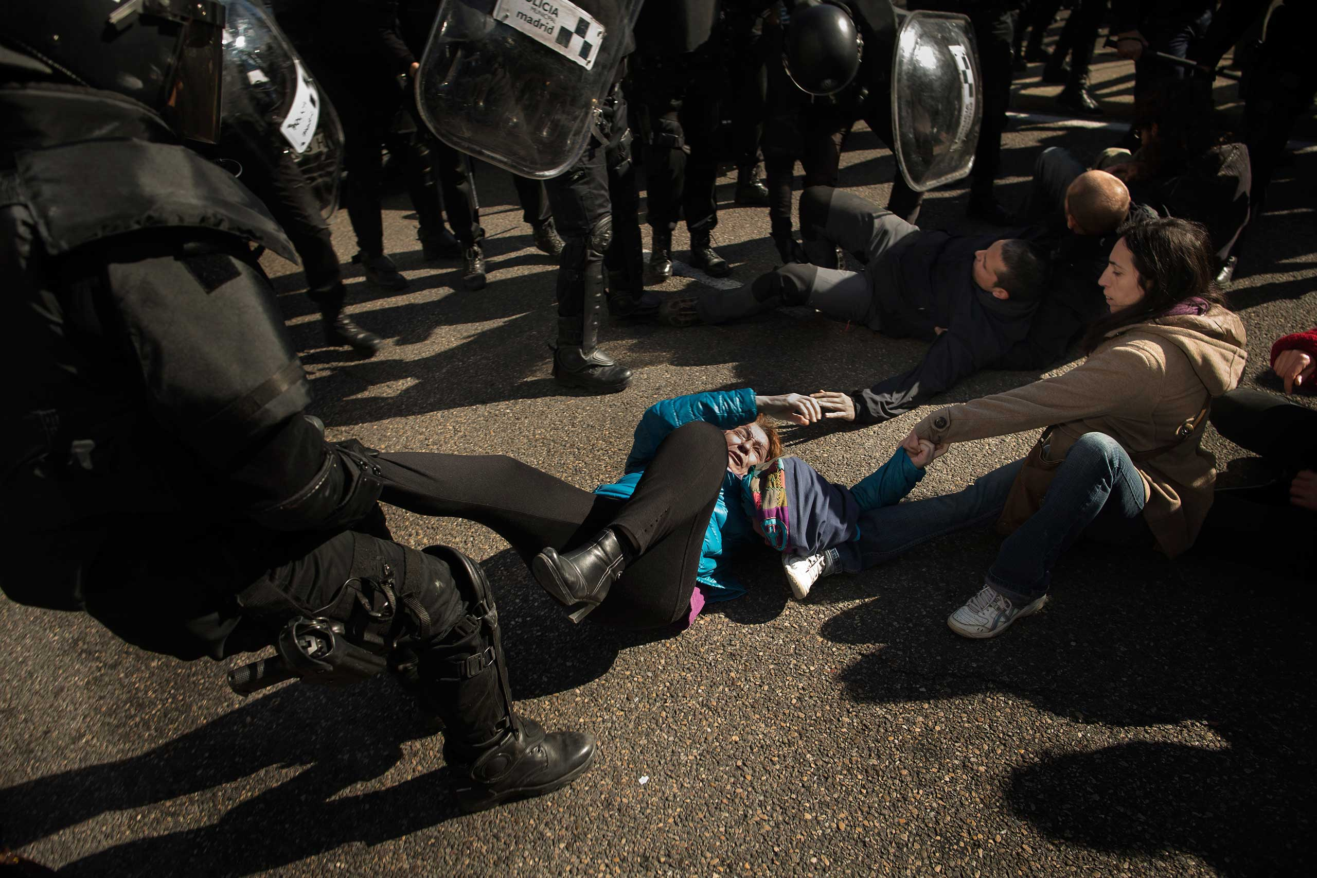 Riot Police remove housing rights activists as they try to stop Luisa Gracia Gonzalez and her family's eviction and the demolition of their house by a forced expropriation in Madrid. Feb. 2015.
