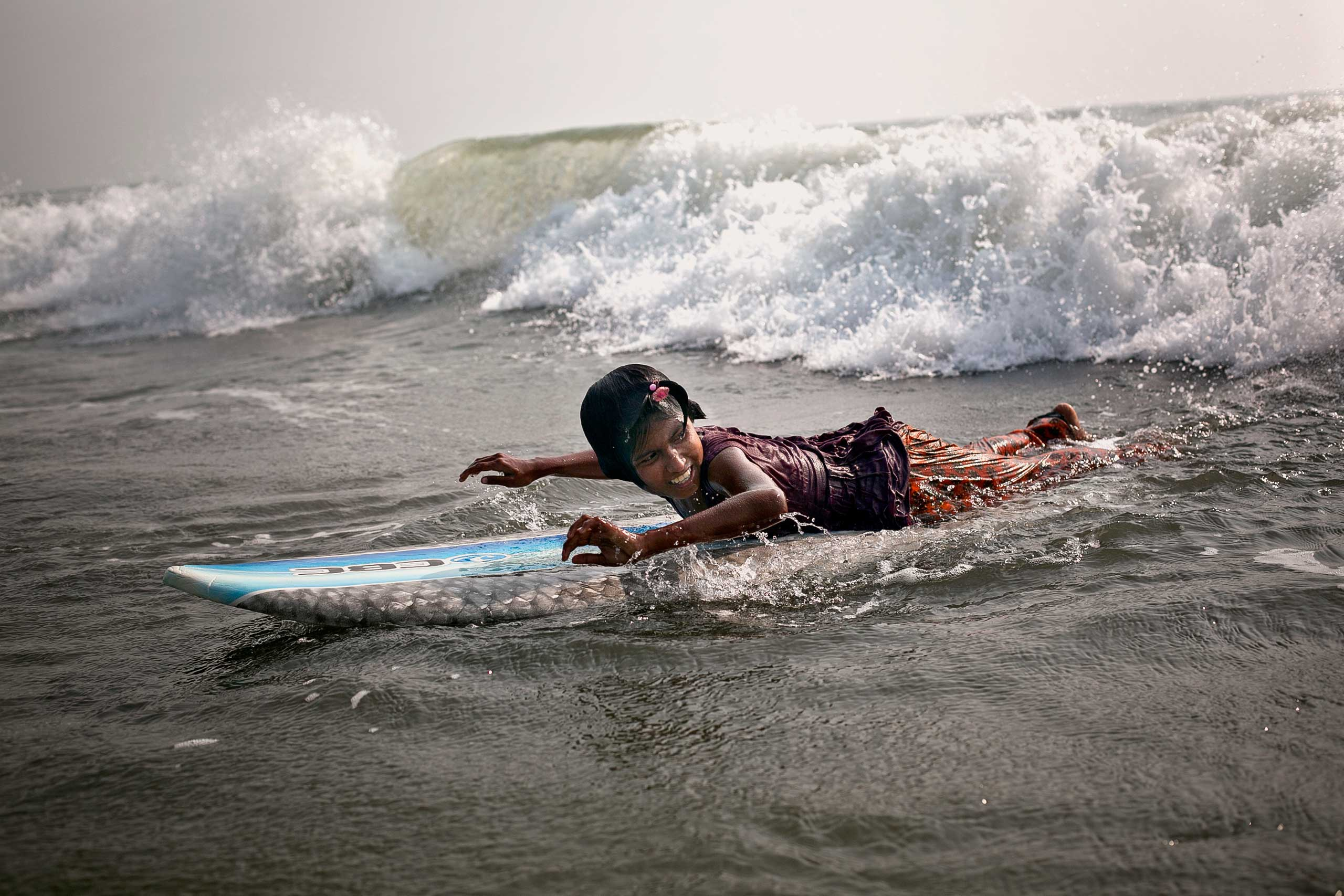Ten-year-old Johanara surfs. The Bangladeshi surf girls are a group of eight outgoing and spunky girls ranging in ages 10 to 13 years old, who live and work in Cox's Bazar, Bangladesh. Poverty is forcing them into an early adulthood, as they are obligated to shoulder the responsibility of earning money to help feed their families. Early each morning, rain or shine, they leave their homes and make their way to the beach, where they work selling jewelry and eggs until late into the night before returning home. Their families are unable survive without the girls' income.