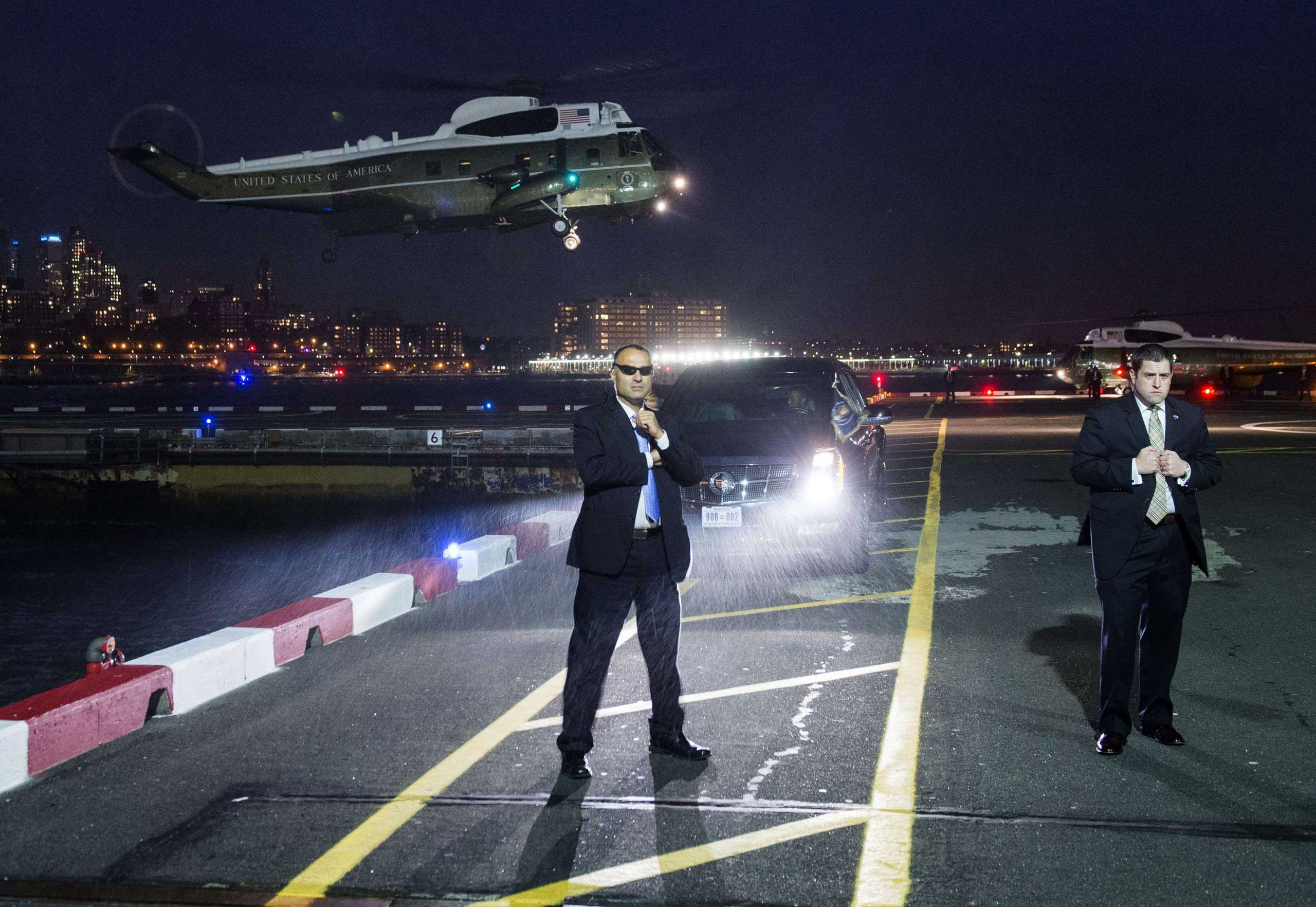 U.S. Secret Service Agents stand guard as Marine One, with U.S. President Barack Obama on board, prepares to land at the Downtown Manhattan Heliport in New York, N.Y. President Obama is traveling to attend Democratic fundraisers. Nov. 2, 2015.