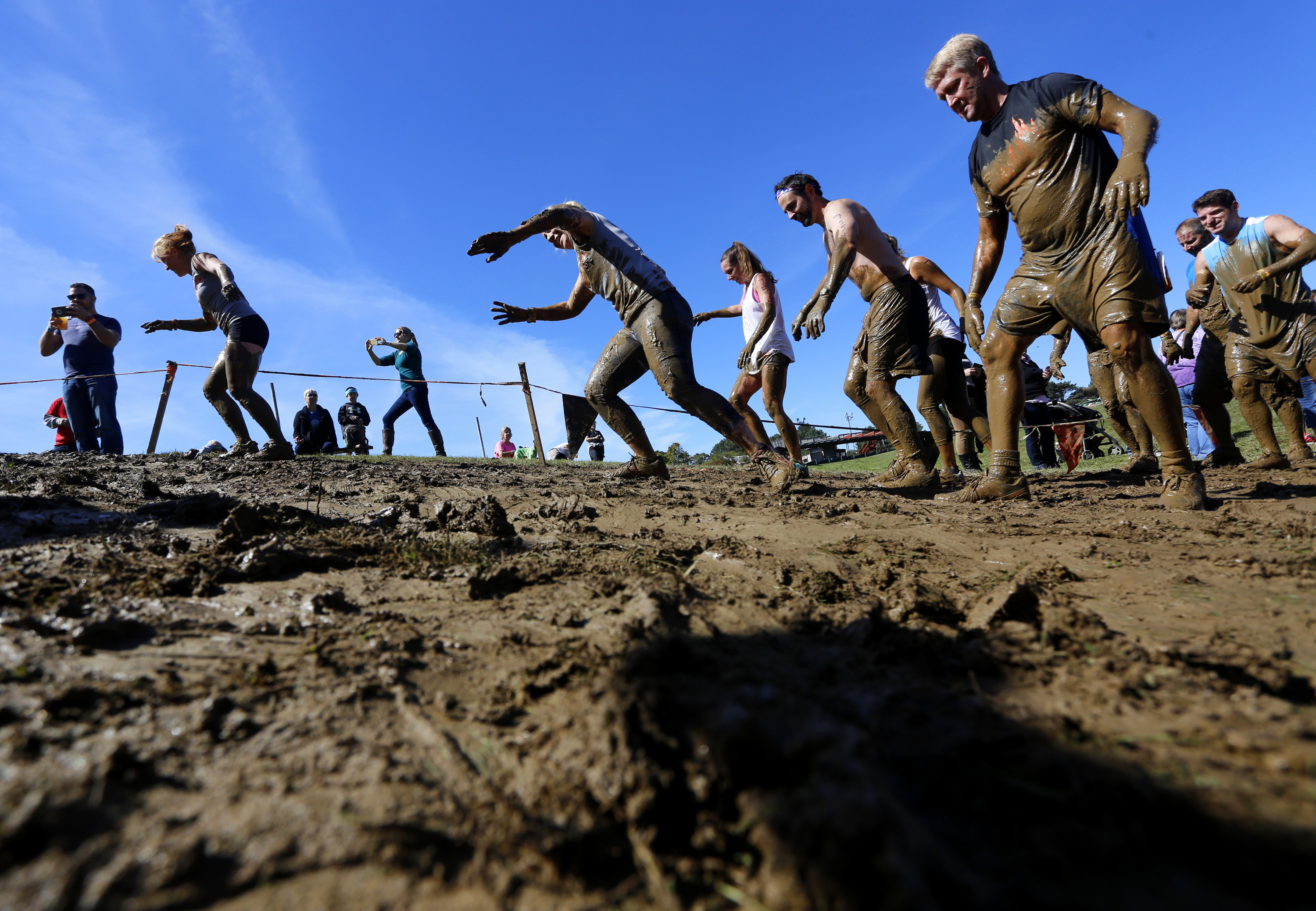 Participants climb a muddy hill after crawling through the  Kiss of Mud 2.0  obstacle during the Tough Mudder obstacle course on Sept. 26, 2015.