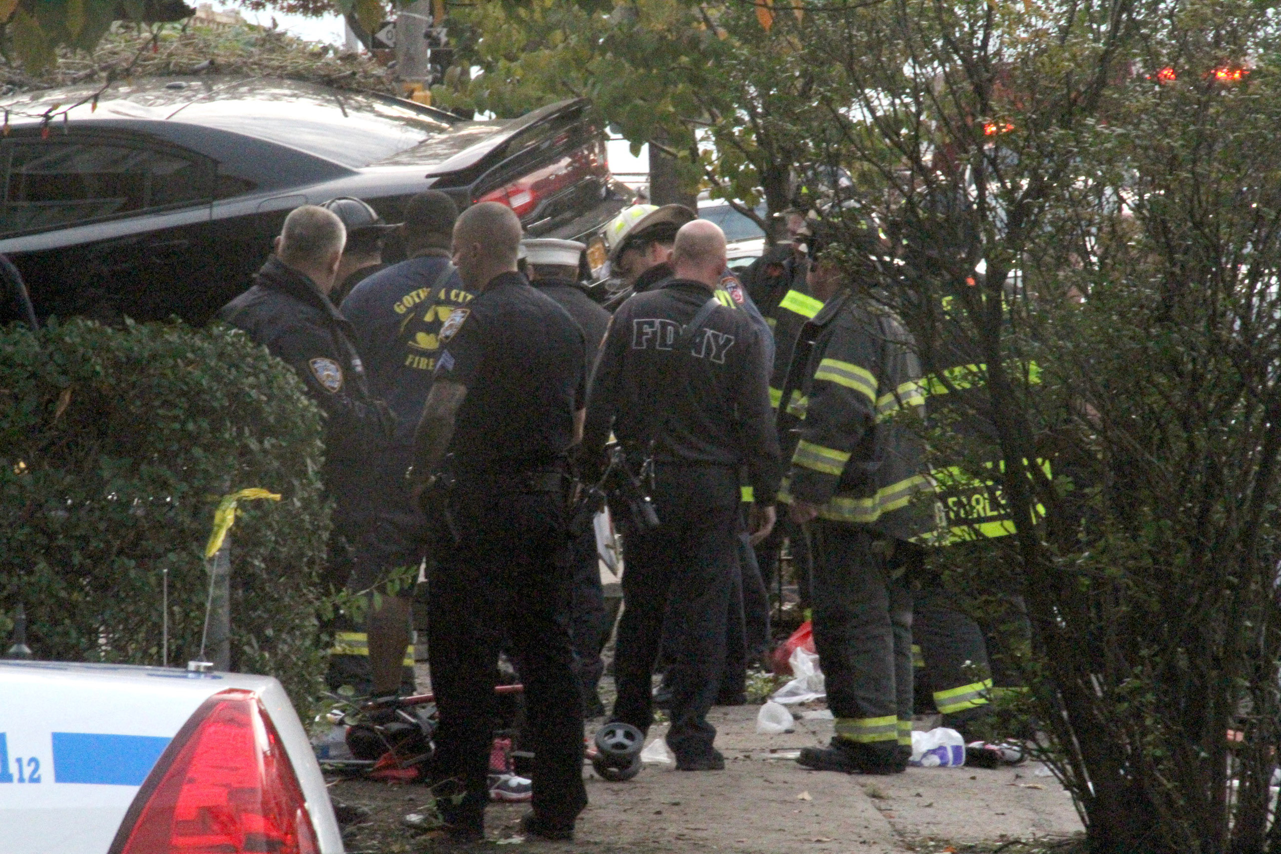 First responders examine an automobile after its driver lost control and plowed into a group of trick-or-treaters, killing three people and injuring several, in the Bronx, N.Y., on Oct. 31, 2015.