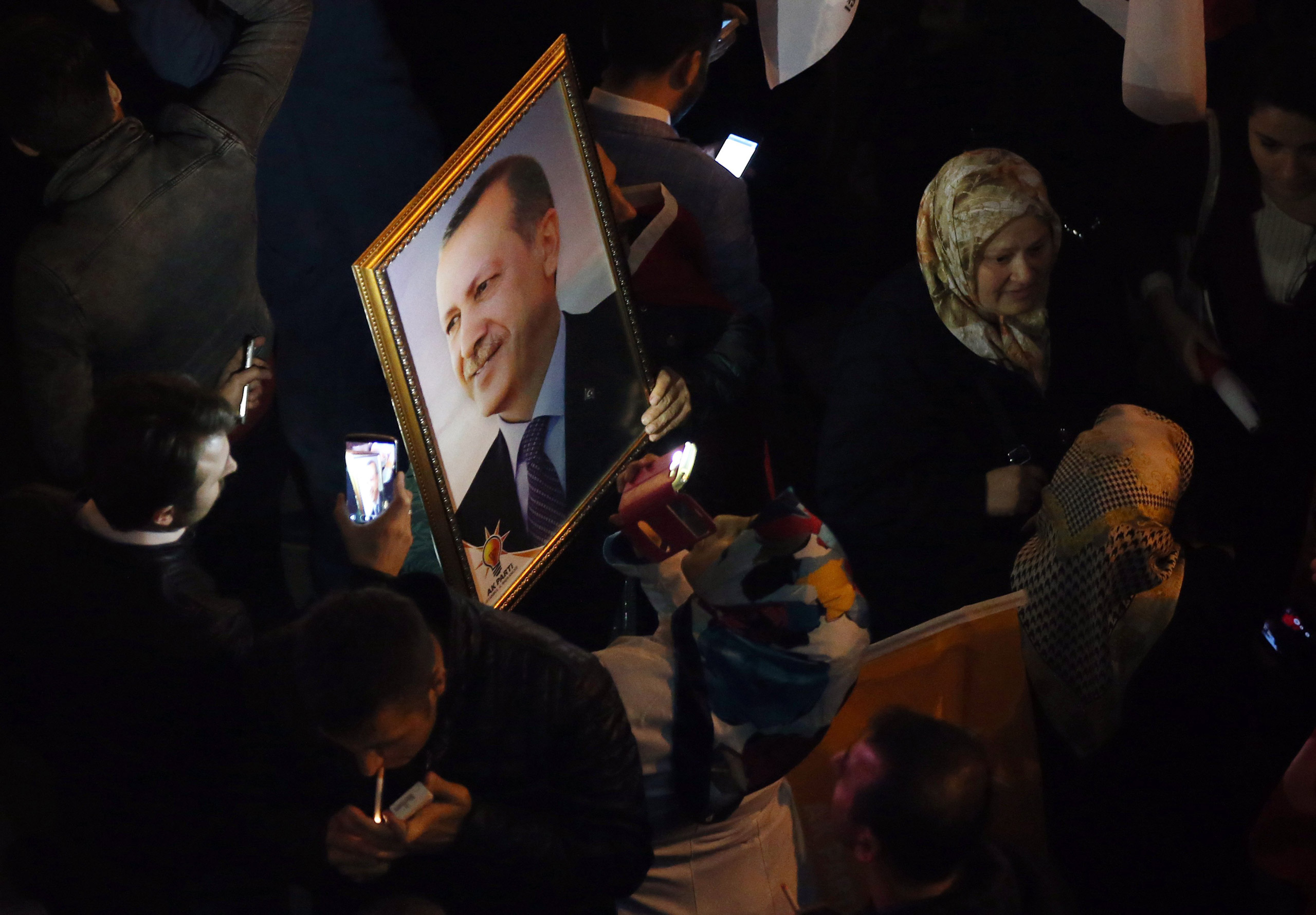 Supporters of the Justice and Development Party, (AKP), hold a portrait of Turkey's President Recep Tayyip Erdogan as they celebrate in front the AKP headquarters in Istanbul, on Nov. 1, 2015.