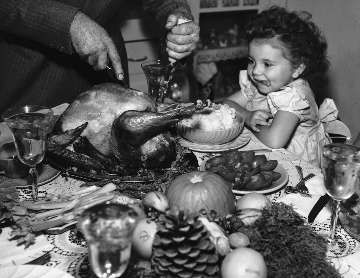 circa 1945:  A little girl sits at a table laden with dishes on Thanksgiving, watching anxiously as a man carves the turkey.