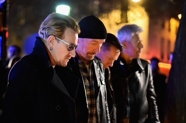 Bono and band members of U2 pay their respects and place flowers on the pavement near the scene of the Bataclan Theatre terrorist attack on November 14, 2015 in Paris, France.