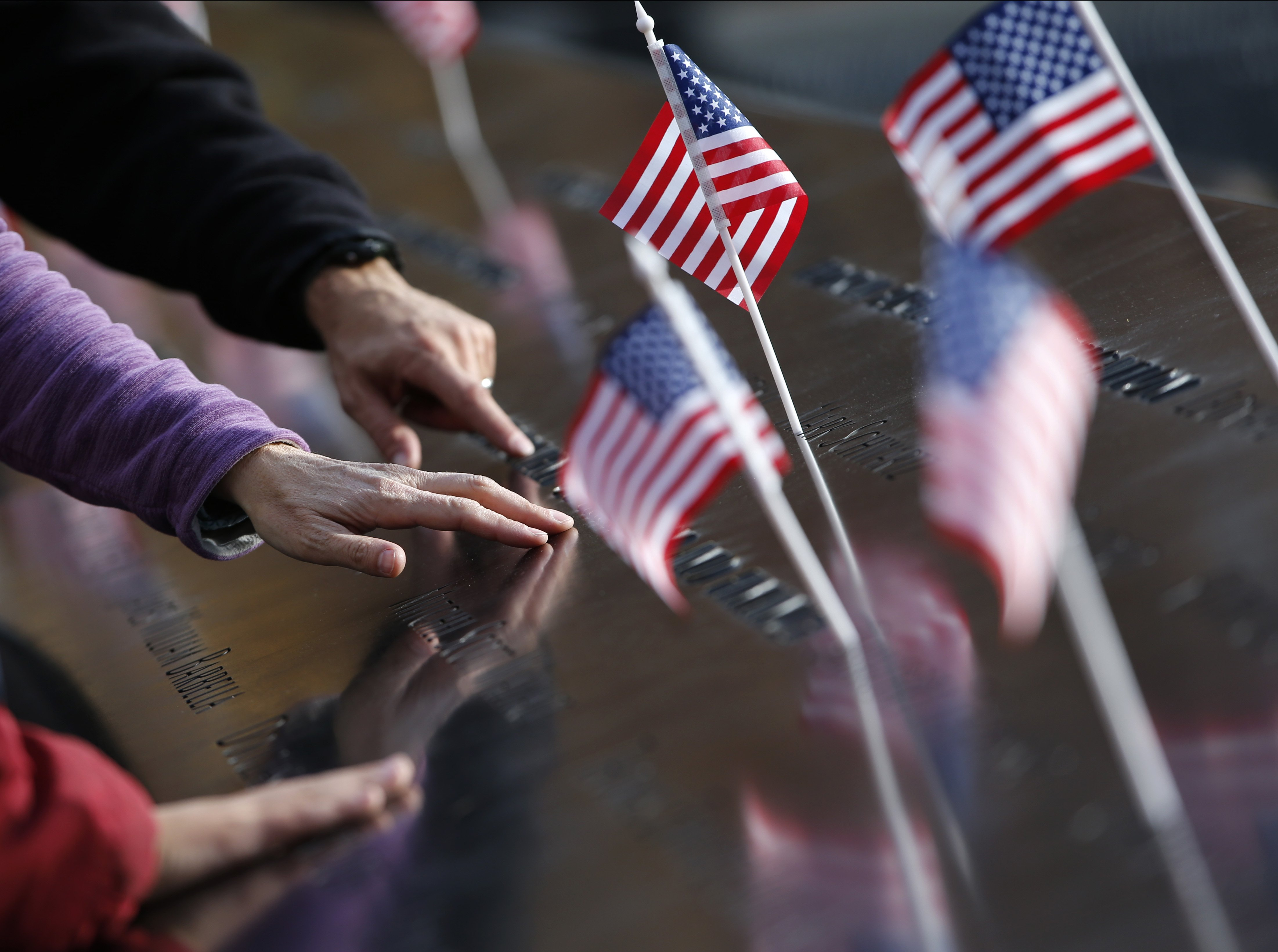 Hands reach out to touch the names inscribed at the South Pool of the 9/11 Memorial in New York City on Nov. 9, 2015.