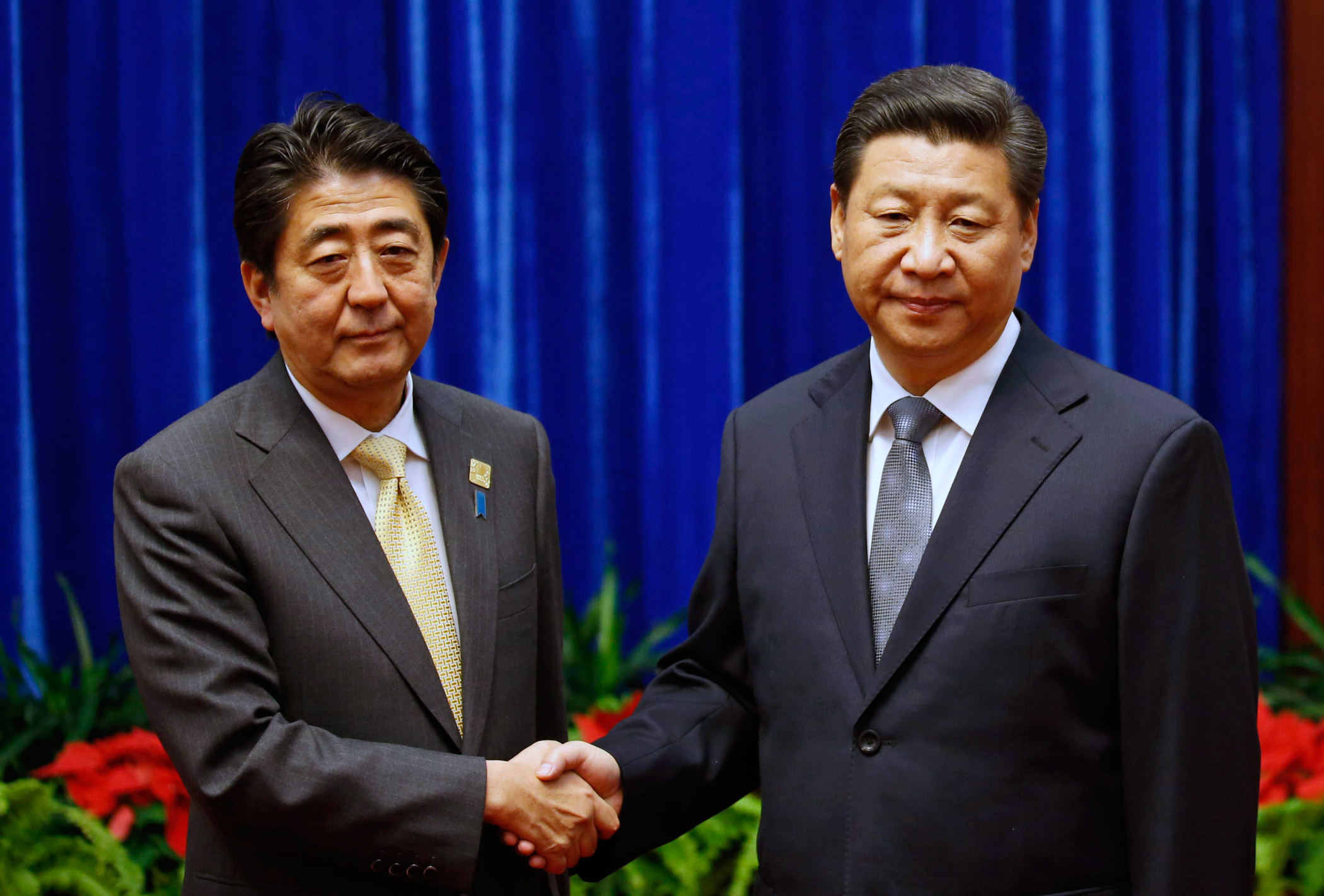 Chinese President Xi Jinping, right, shakes hands with Japanese Prime Minister Shinzo Abe, during their meeting on the sidelines of the Asia Pacific Economic Cooperation (APEC) meetings on Nov. 10, 2014 in Beijing.