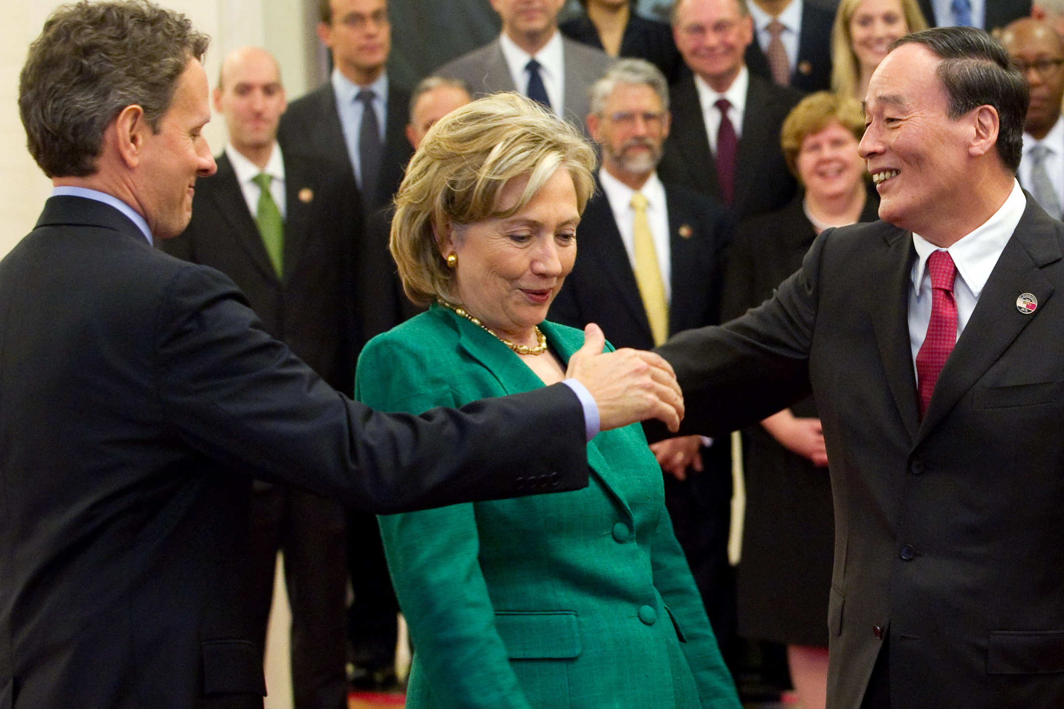 Chinese Vice-Premier Wang Qishan, right, tries to shake hands with U.S. Secretary of Treasury Timothy Geithner as then-Secretary of State Hillary Clinton passes through during the US-China Strategic & Economic Dialogue in Beijing on May 24, 2010.