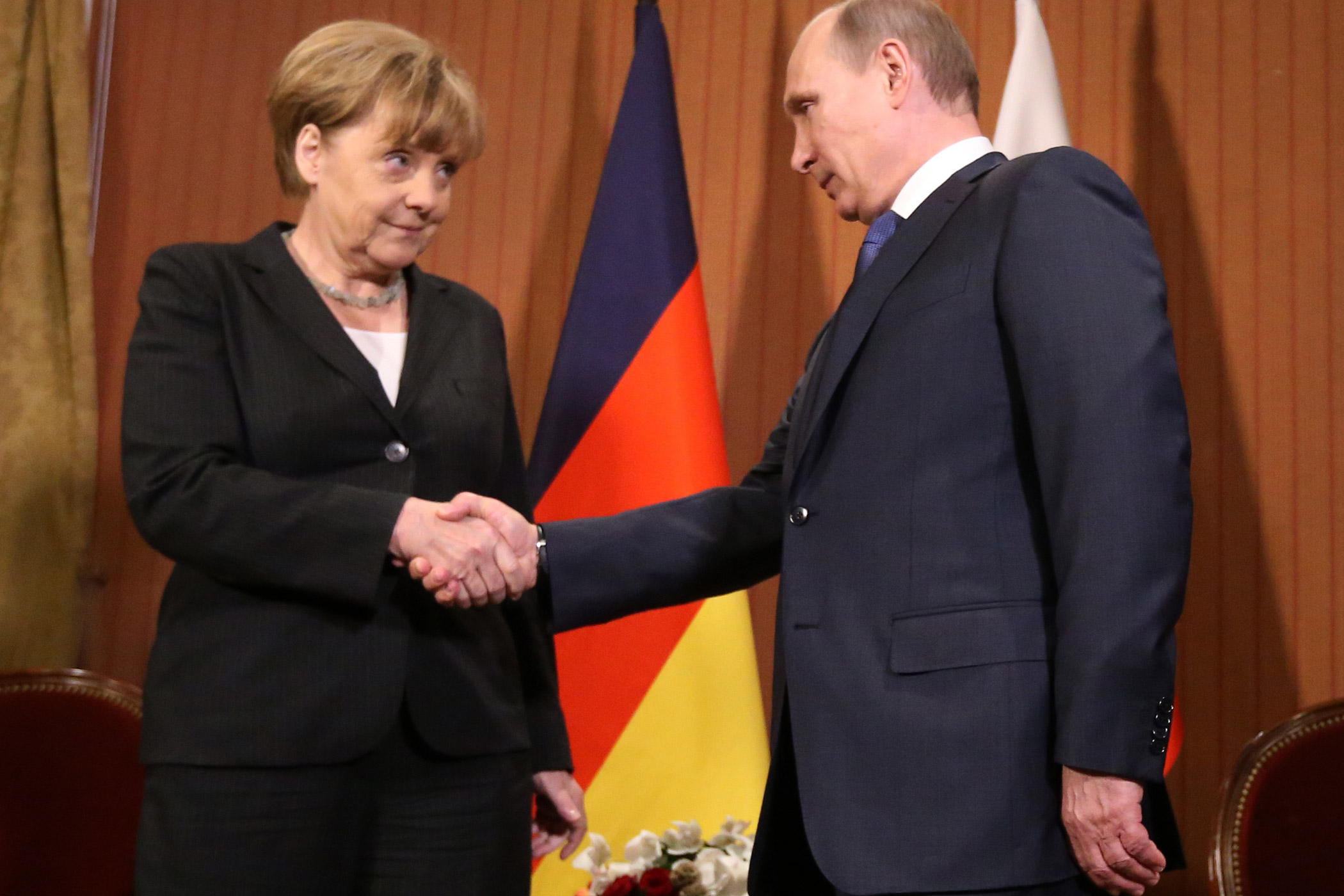 Russian President Vladimir Putin shakes hands with German Chancellor Angela Merkel of Germany during D-Day anniversary celebrations on June 6, 2014 in Deauville, France.