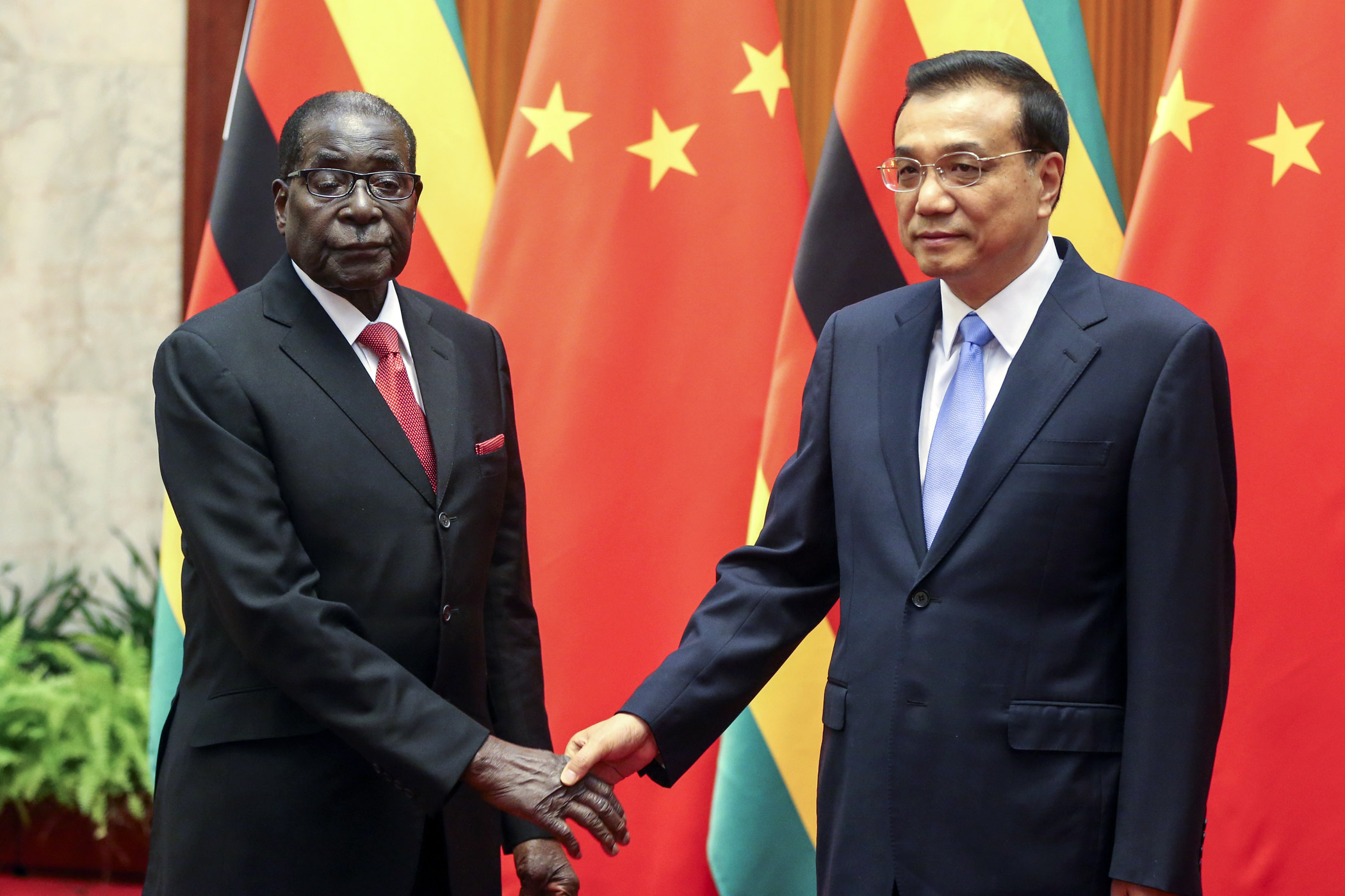 Zimbabwean President Robert Mugabe, left, meets Chinese Premier Li Keqiang at the Great Hall of the People on Aug. 26, 2014 in Beijing.
