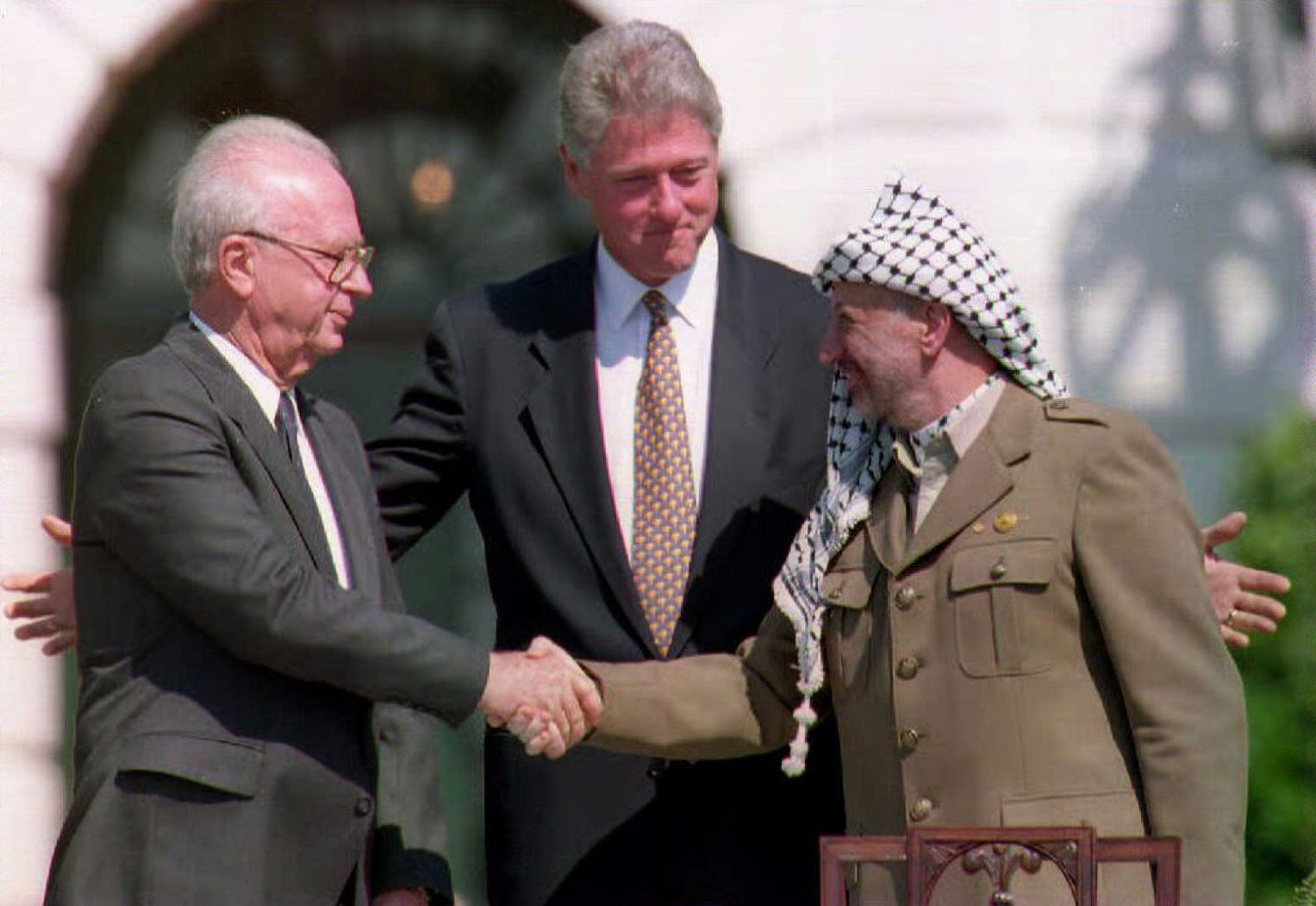 U.S. President Bill Clinton (C) stands between PLO leader Yasser Arafat (R) and Israeli Prime Minister Yitzahk Rabin (L) as they shake hands at the White House in Washington D.C. on Sept. 13, 1993.