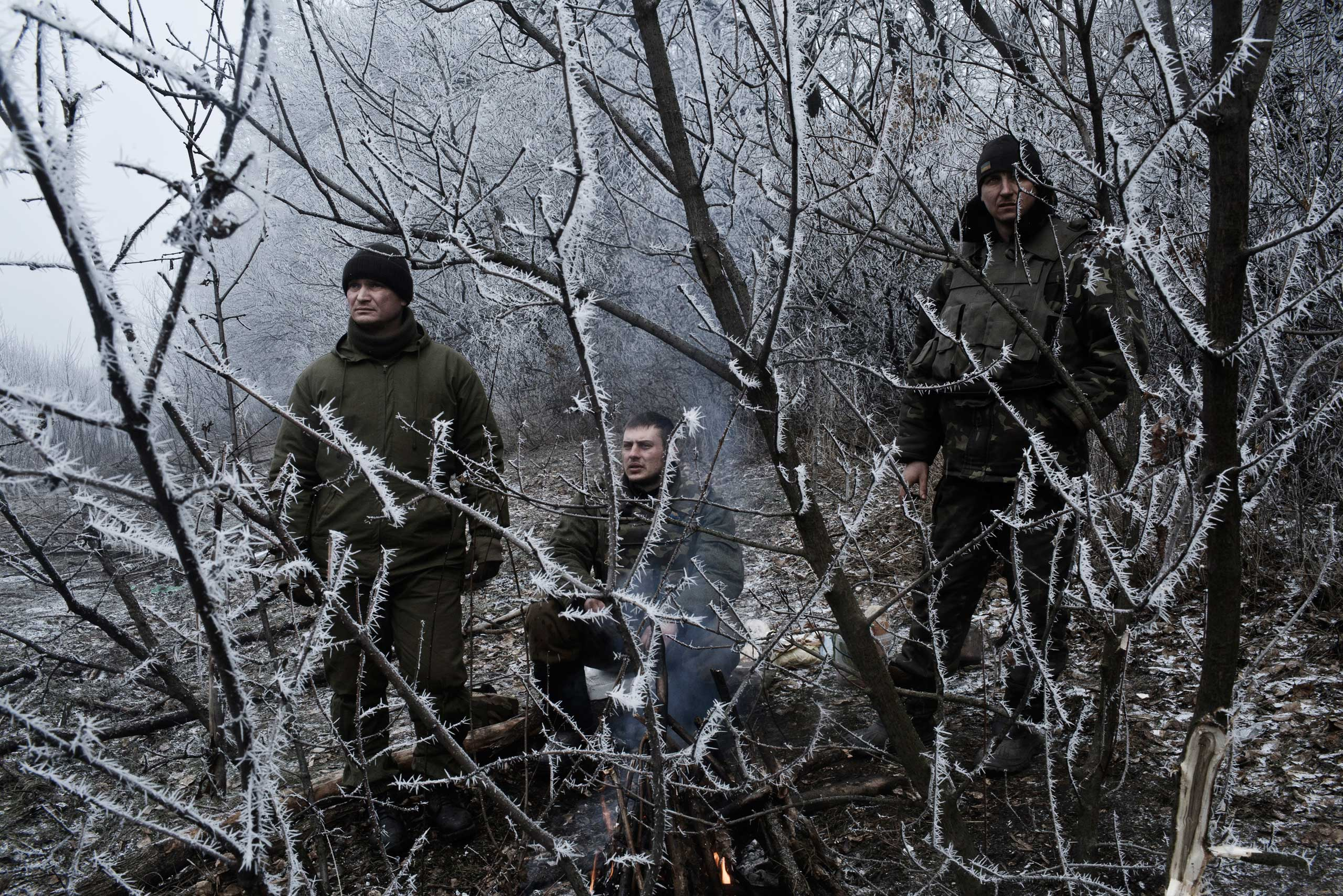 Ross McDonnell:                                 Debaltsevo, in Eastern Ukraine, had been encircled by Pro-Russian forces that had mounted a massive offensive to take the strategic town. Rumors swirled that up to 6,000 Ukrainian forces were trapped inside. The battle, nearing its end, had raged for weeks.                                                               We covered the situation as best we could from the closest town on the Ukrainian side, Artemivsk, convoying up and down the dangerous road between the cities, passing the carcasses of destroyed vehicles, gleaning information and photos from the muddied troops as they retreated, or awaited orders, warming themselves by small fires.                                                              That morning, it seemed as though the fight for Debaltsevo had been lost to the Pro-Russian Separatists. We were on the road early, in the blue half-light. The hoar frost had enveloped the countryside and fog sat low over the road. Between lines of tanks, GRAD rocket launchers and military transports, a group of soldiers played football in the road, their breath catching the frozen air.                                                               It was impossible not to think of World War I in that static, etheral moment. The ice and fog seemed to blanket the landscape and indeed, the emotions of the scene, temporarily delaying the shock of defeat and the reveal of the aftermath.                                                                Three Ukrainian National Guardsmen, off to the side of the road, seemingly reflect this sentiment too, their expressions in the resulting photograph, perhaps silently weighing up the consequences of war.                                                               This photo was taken along a road leading to Debaltseve in Artemivsk, Ukraine on Feb. 15, 2015.