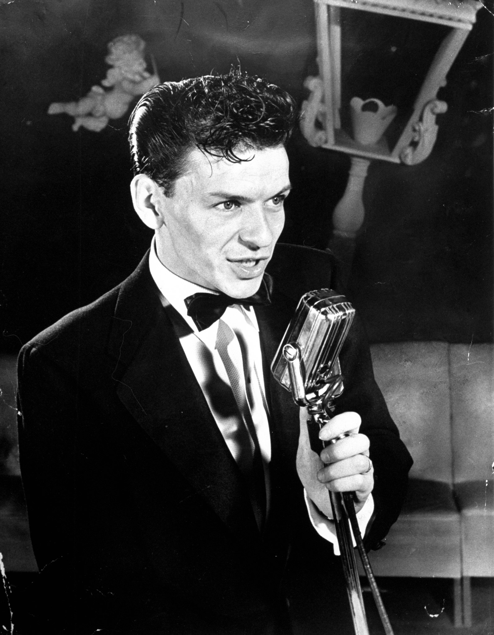 "25-year-old Frank Sinatra poised at the microphone, singing ""As Time Goes By"" at the Riobamba nightclub, 1943."