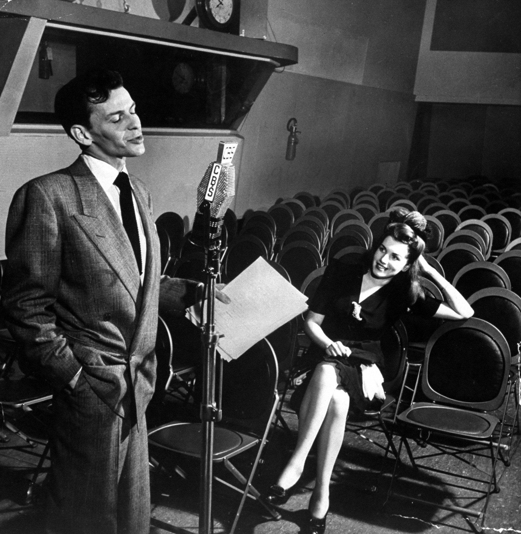 "Sinatra singing ""Close to You"" in CBS radio broadcasting studio as admirer Rita Stearns, the winner of the ""Why I Like Frank Sinatra"" contest, looks on, 1944."