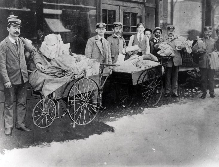City letter carriers pose with handcarts used to collect and transport mail, 1885.