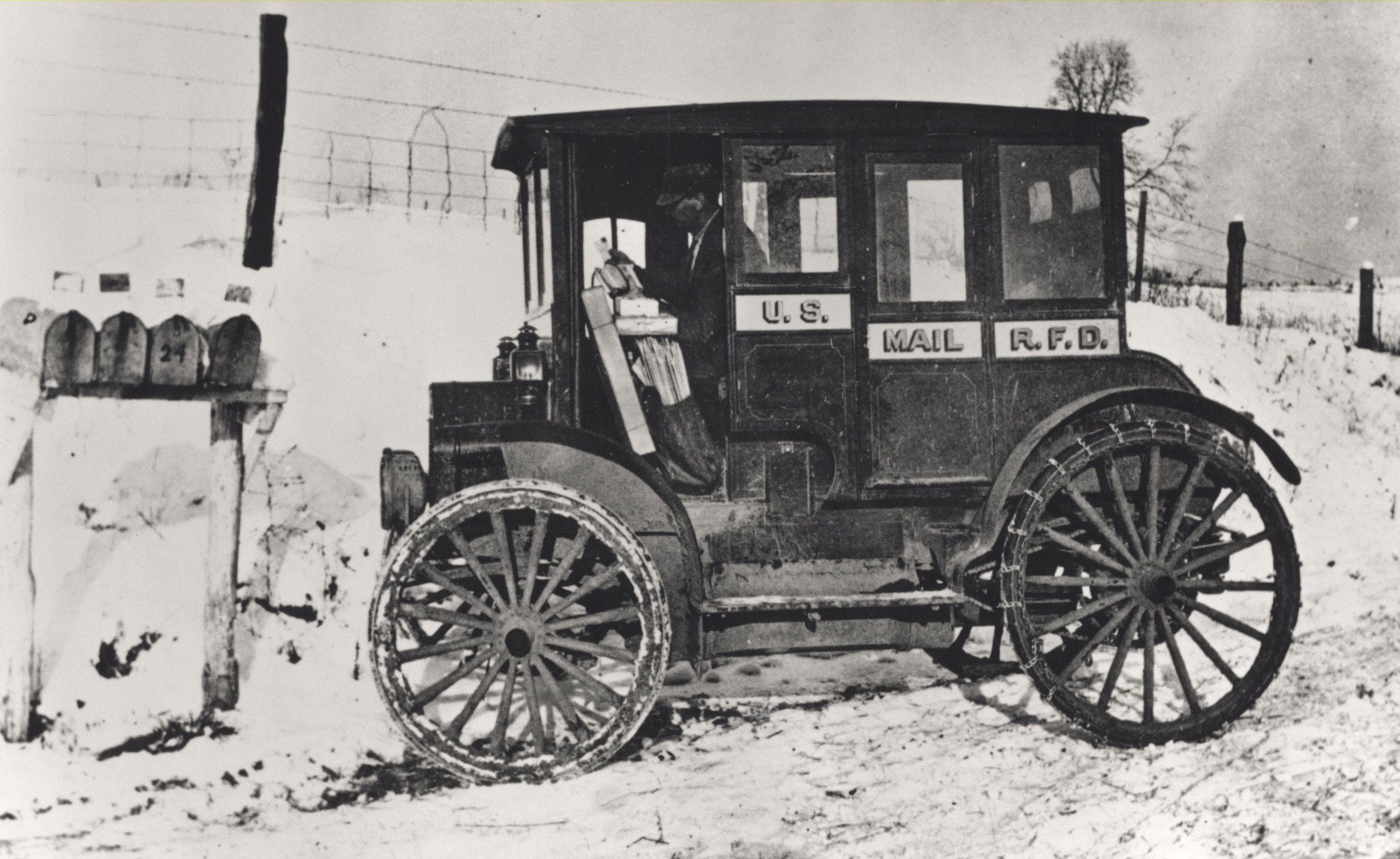 Postal officials encouraged Rural Free Delivery (RFD) carriers to replace their horses and wagons with electric-motored vehicles,  but this 1910 postal worker was surely only able to complete his wintertime rounds thanks to a snow-plowed road. Automobiles were not yet adequate replacements for horses and sleds on rural roads.
