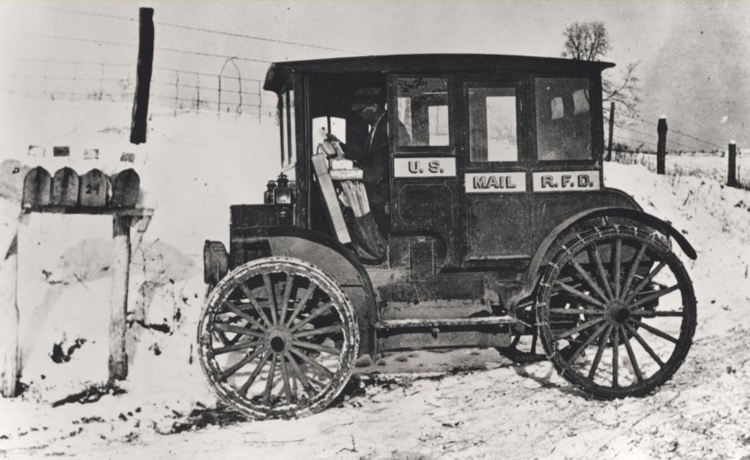 Postal officials encouraged Rural Free Delivery (RFD) carriers to replace their horses and wagons with the latest in transportation technology. This unidentified carrier painted his early electric-motored vehicle in the same paint and identification scheme as the RFD wagons of the era. He is, no doubt, only able to complete his wintertime rounds thanks to a snow-plowed road. Automobiles were not yet adequate replacements for horses, wagons, and sleds on rural roads. 1910.