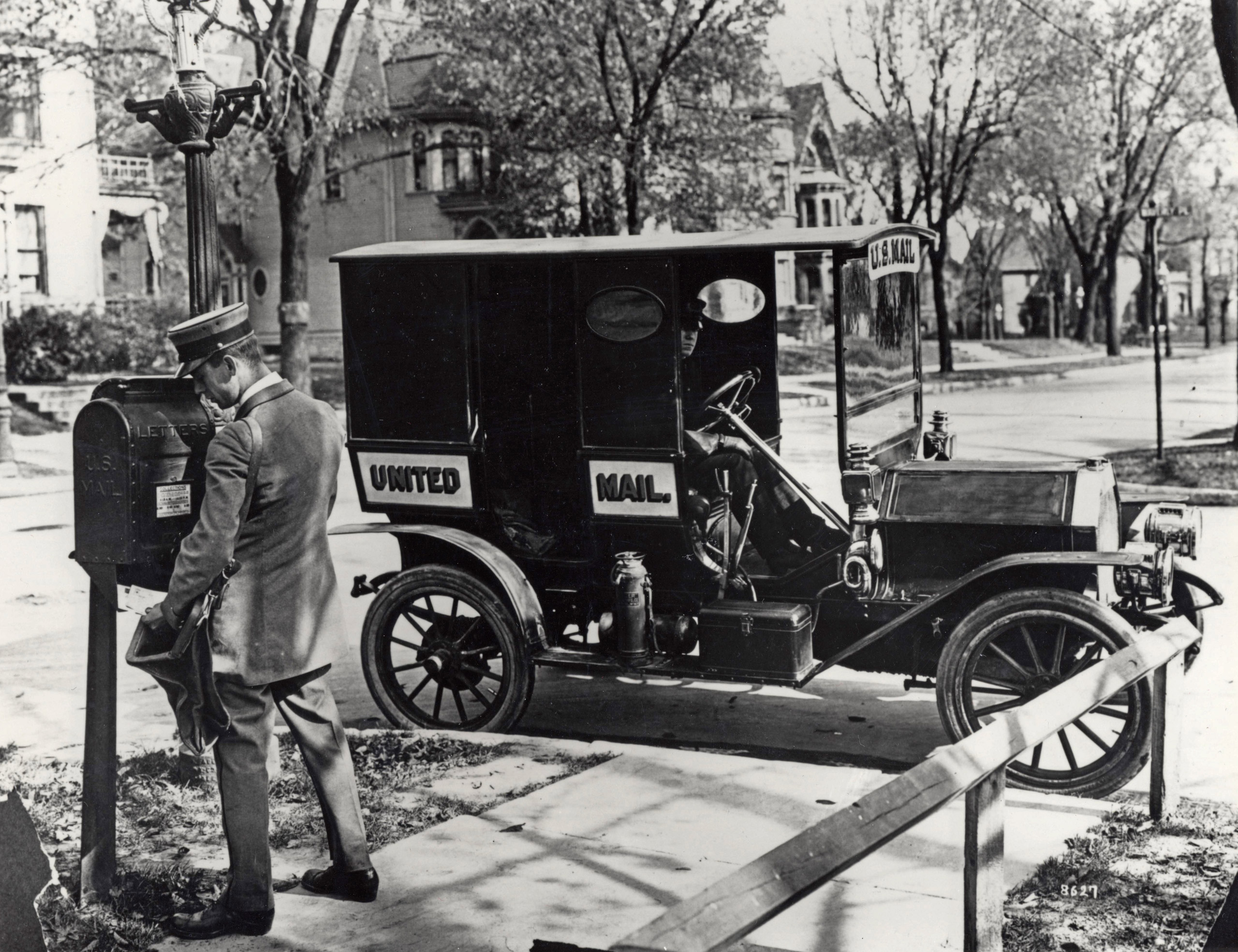 A letter carrier collecting mail from a sidewalk mail collection box. His mail truck is parked at the curb. 1915.