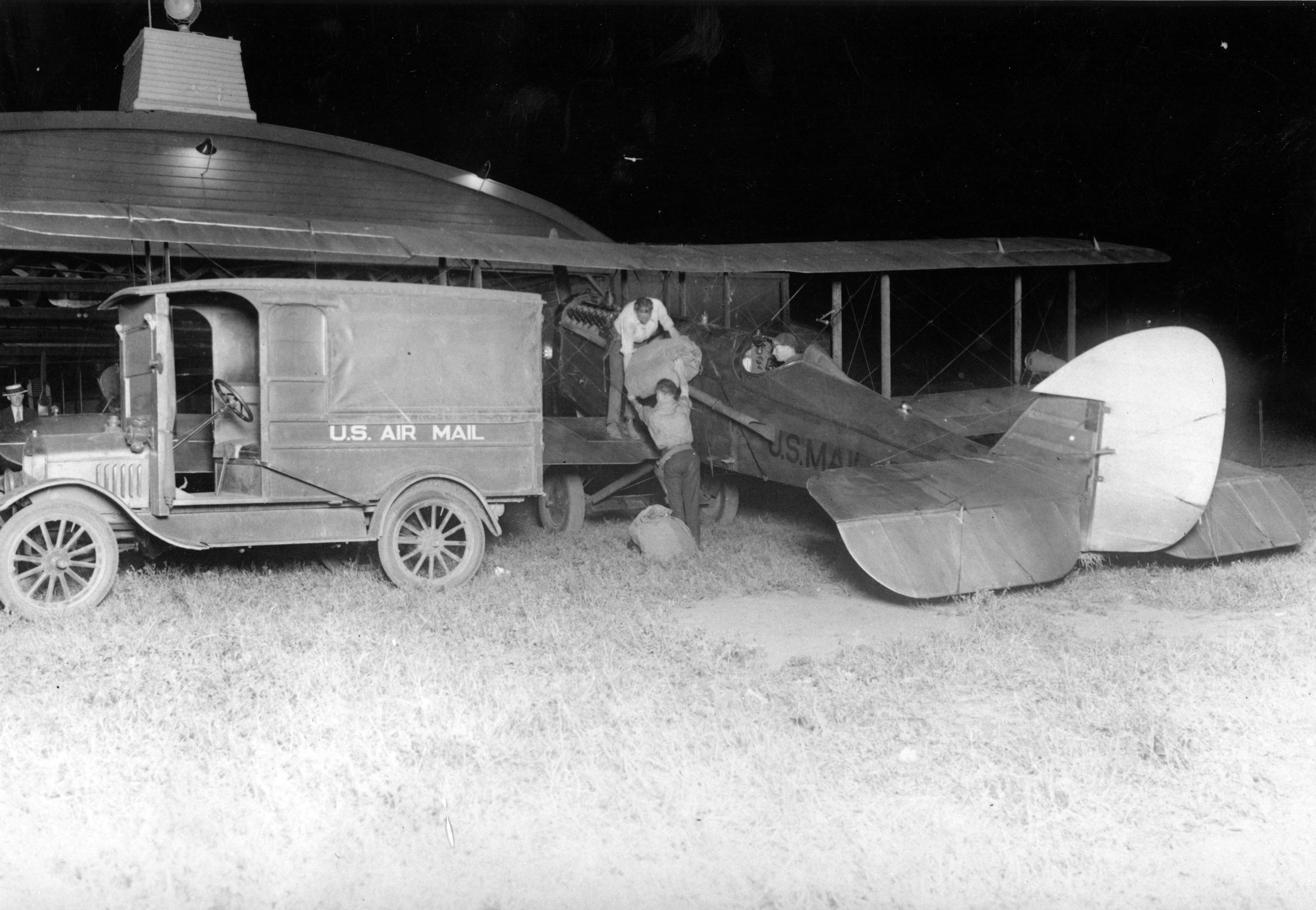 Postal employees loading mail into a de Havilland mail airplane at Hadley Field in New Brunswick, N.J. Transcontinental airmail service had begun in the summer of 1924 and was then extended to east coast with the completion of a series of airmail beacons that helped guide pilots across the country.