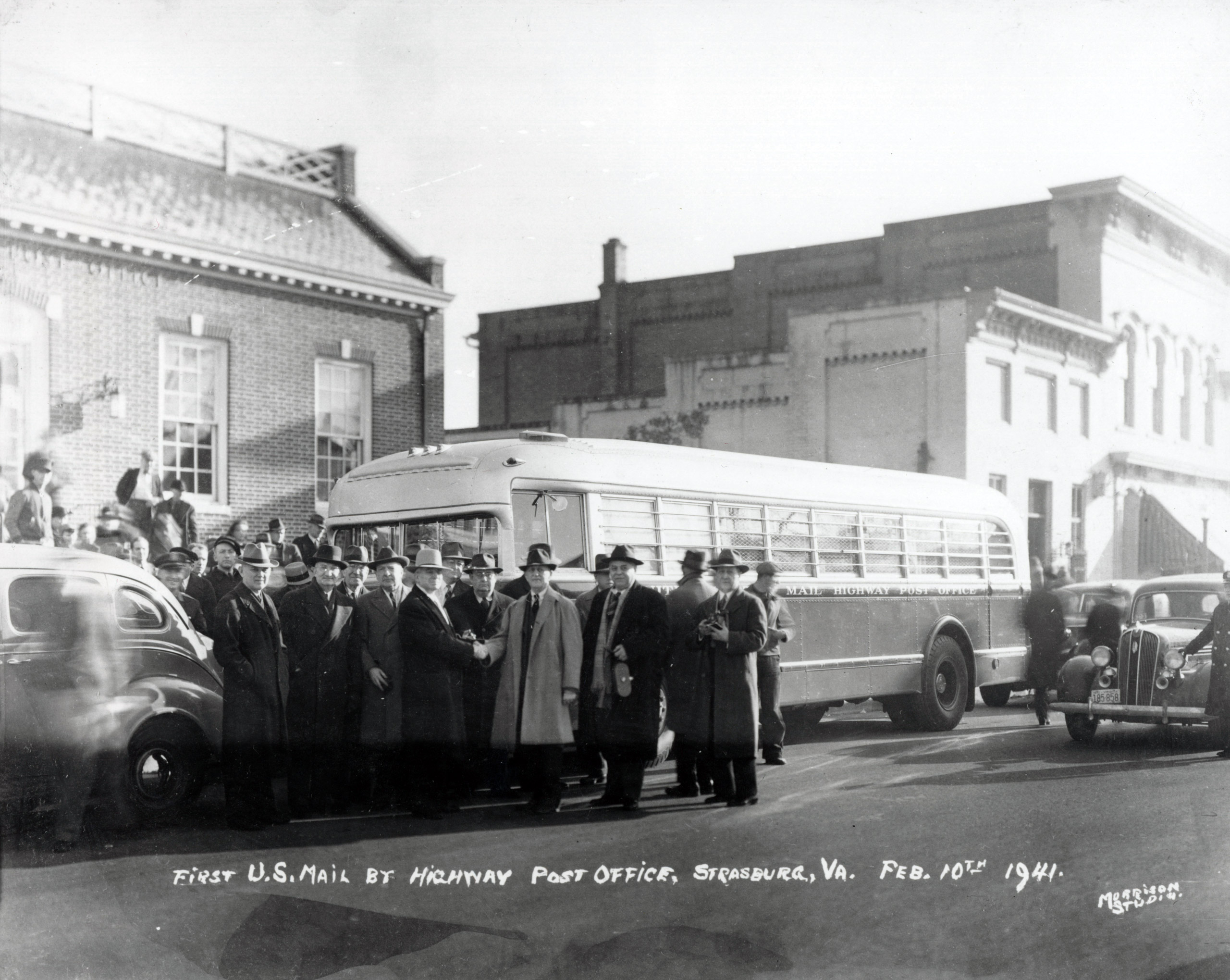 Officials are gathered to welcome the first Highway Post Office bus in Strasburg, Va., on Feb. 10, 1941. By the 1930s, a significant decline in railroad passenger traffic had caused a subsequent decline in the use of railway trains. To fill the void, the postal service transferred some en route distribution from trains to highway buses.