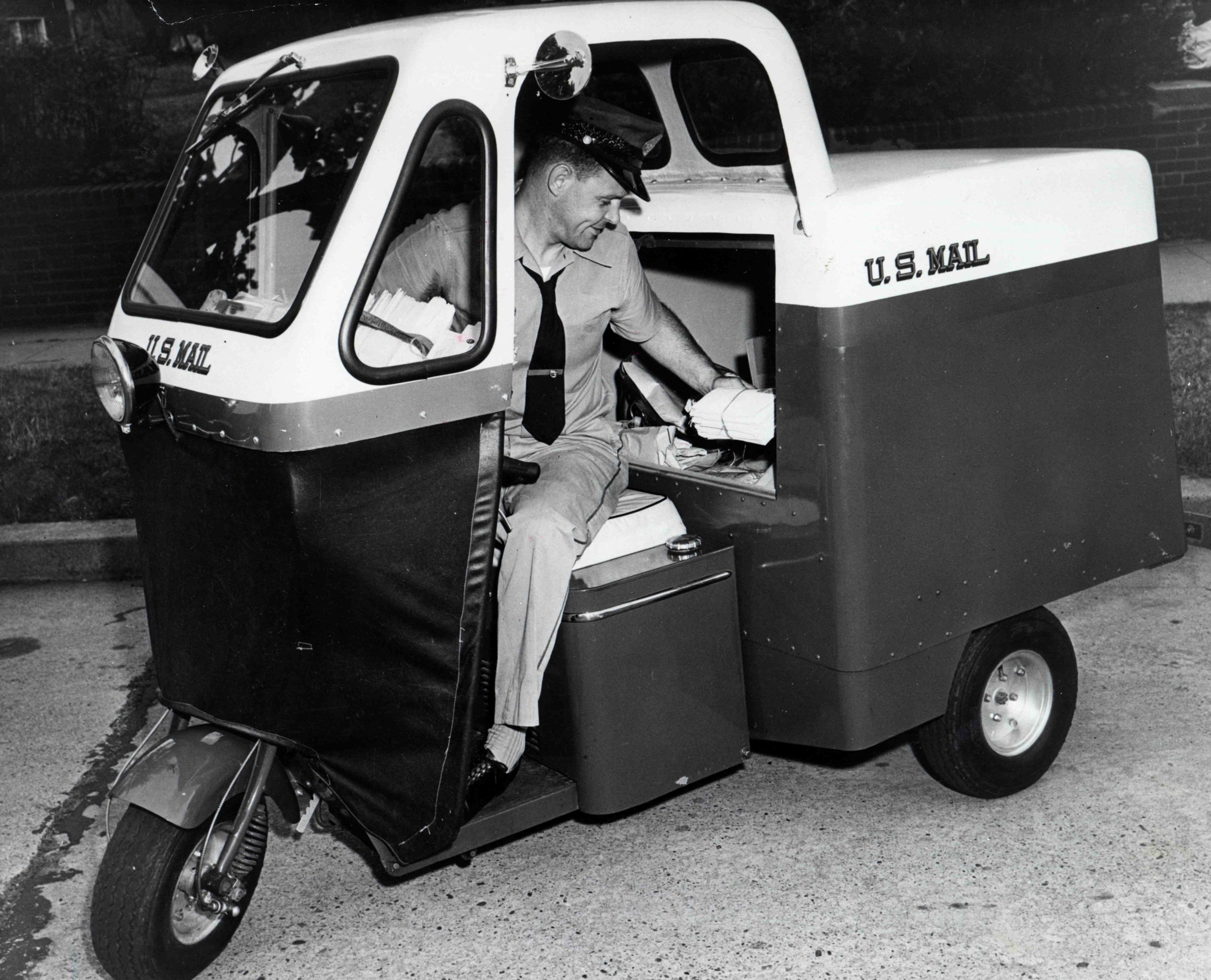 In 1955, a city letter carrier is seated in a three-wheeled  mailster  motor vehicle. Carriers used these vehicles to carry the ever-increasing amounts of mail that was being delivered to American households after end of the Second World War, but they could be immobilized in as little as three inches of snow, did not heat properly and were easily tipped over.