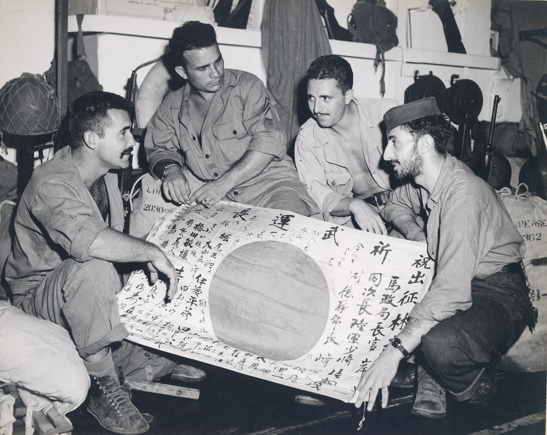 Marines show a sailor a captured Japanese flag while en route home to the States as part of Operation Magic Carpet. This image is part of a photograph album detailing the wartime service of the carrier Intrepid (CV 11) in the Pacific during World War II.