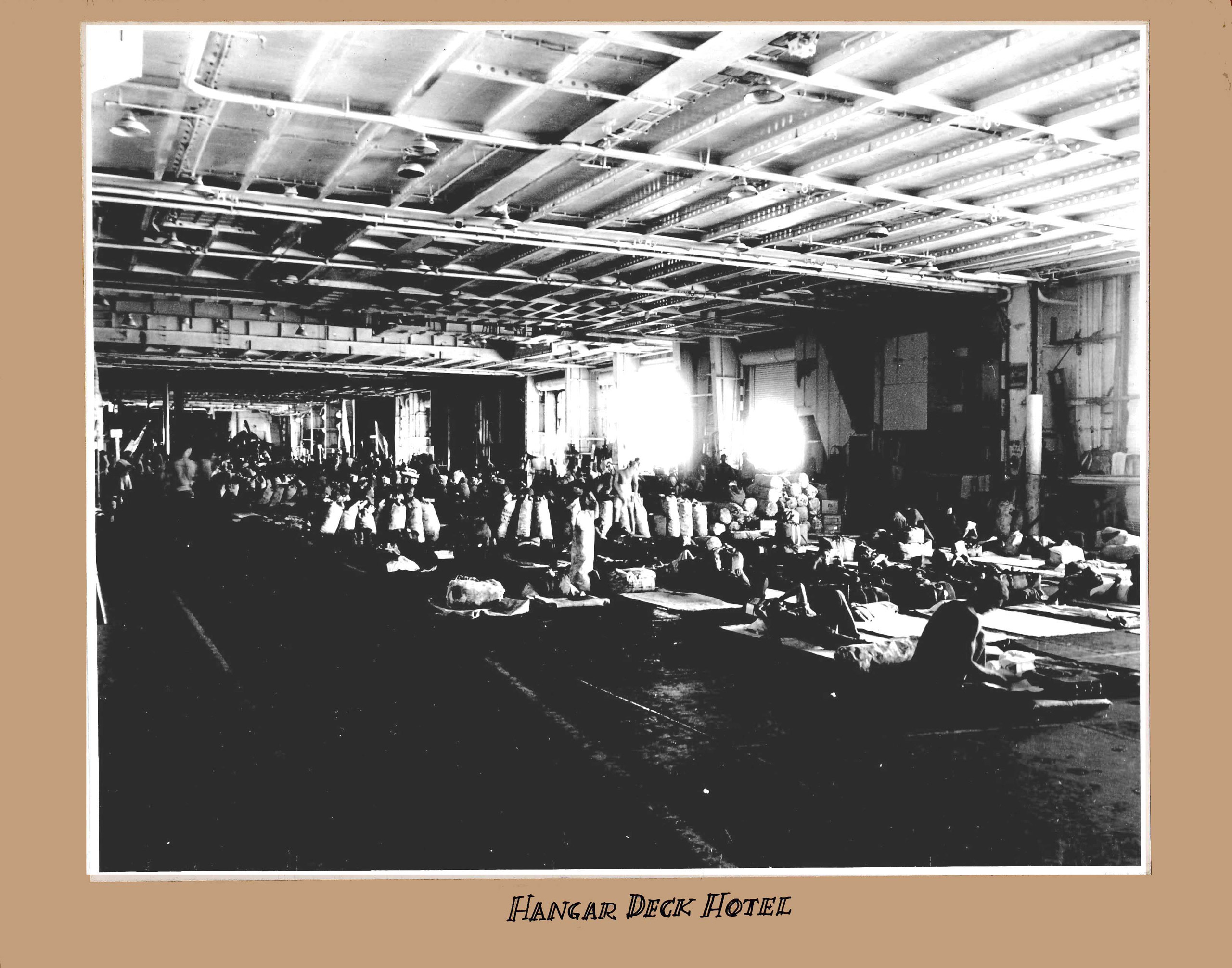 Troops heading back to the States as part of Operation Magic Carpet crowd the hangar deck of Wasp (CV 18). This image is part of a photograph album that was acquired by RADM Joseph C. Clifton during his service as Executive Officer of Wasp (CV 18) during World War II.